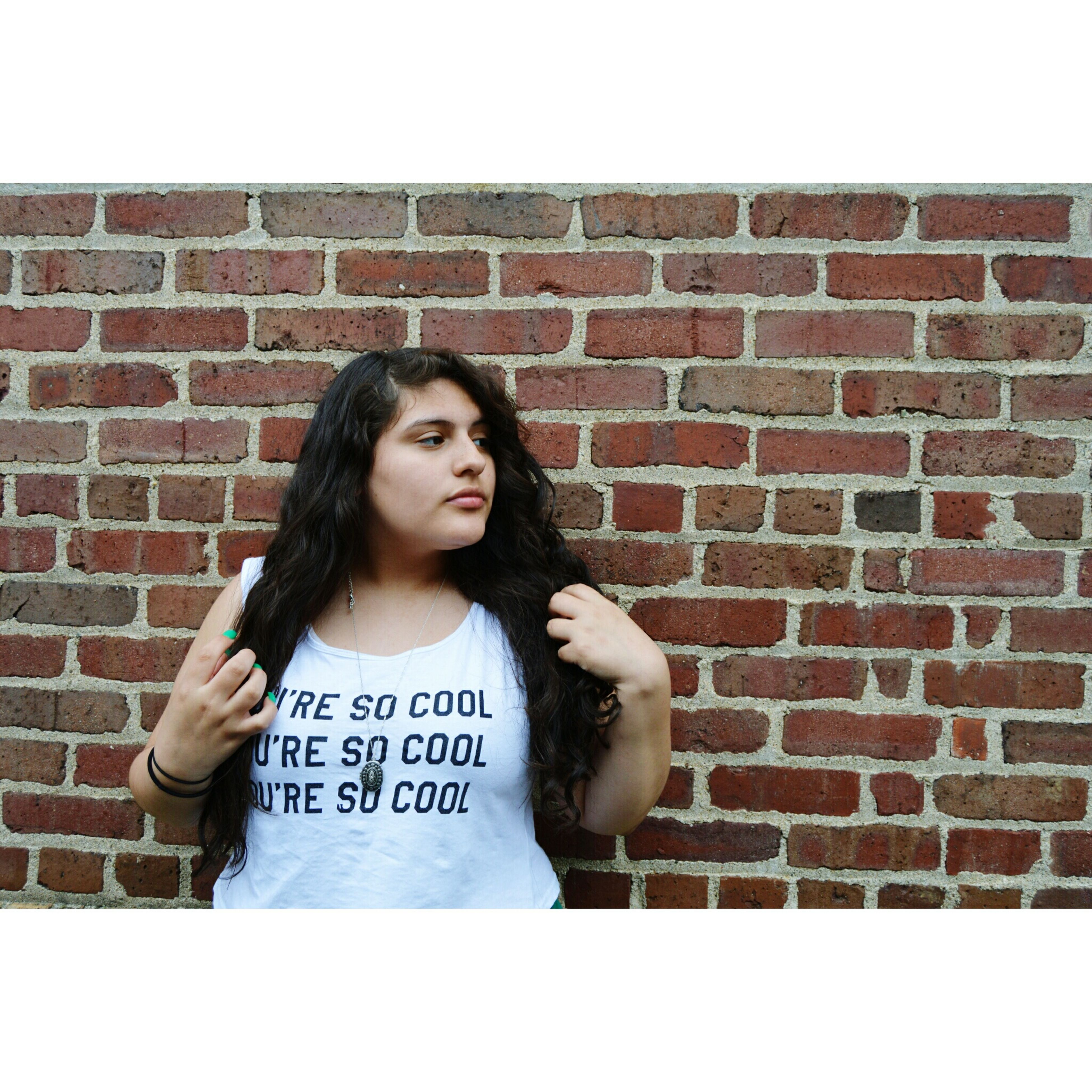 text, person, brick wall, wall - building feature, front view, portrait, western script, looking at camera, young adult, communication, lifestyles, young women, wall, waist up, standing, casual clothing, long hair, happiness