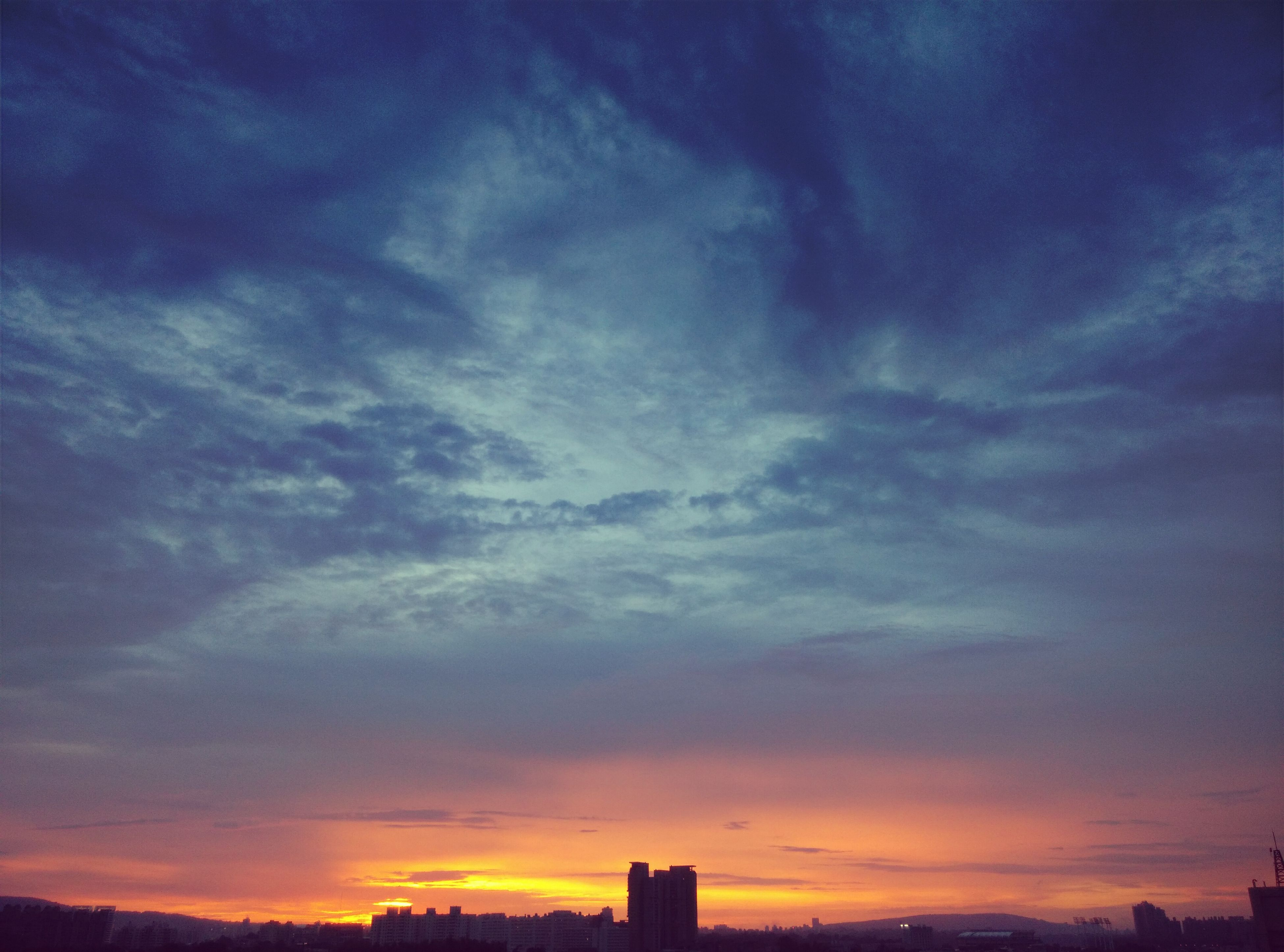 sunset, sky, silhouette, cloud - sky, scenics, beauty in nature, orange color, dramatic sky, tranquility, low angle view, tranquil scene, building exterior, built structure, nature, cloud, architecture, cloudy, idyllic, moody sky, dusk
