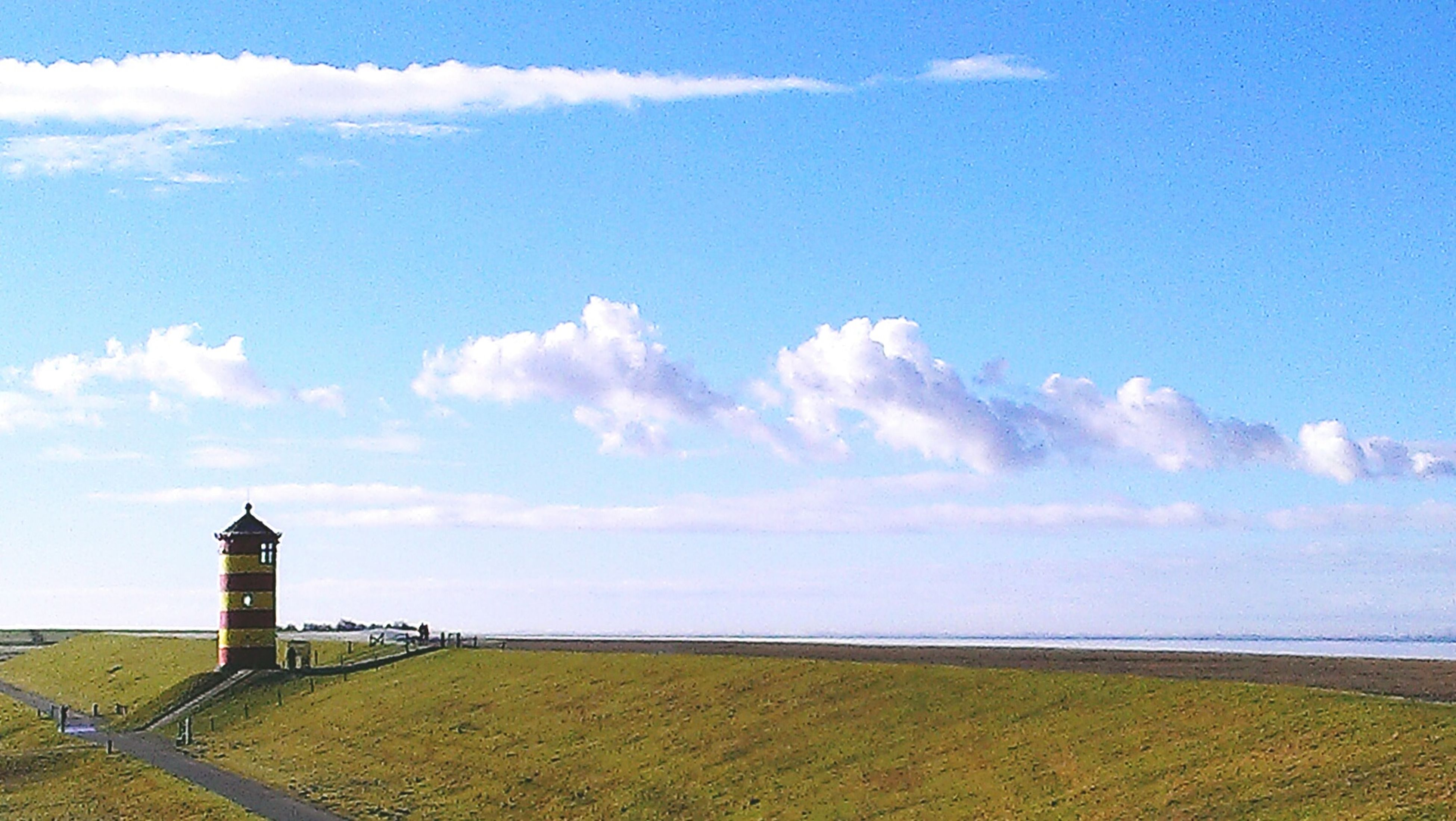 sky, sea, lighthouse, cloud - sky, horizon over water, built structure, scenics, tranquility, cloud, tranquil scene, architecture, guidance, blue, beauty in nature, water, protection, building exterior, nature, grass, safety