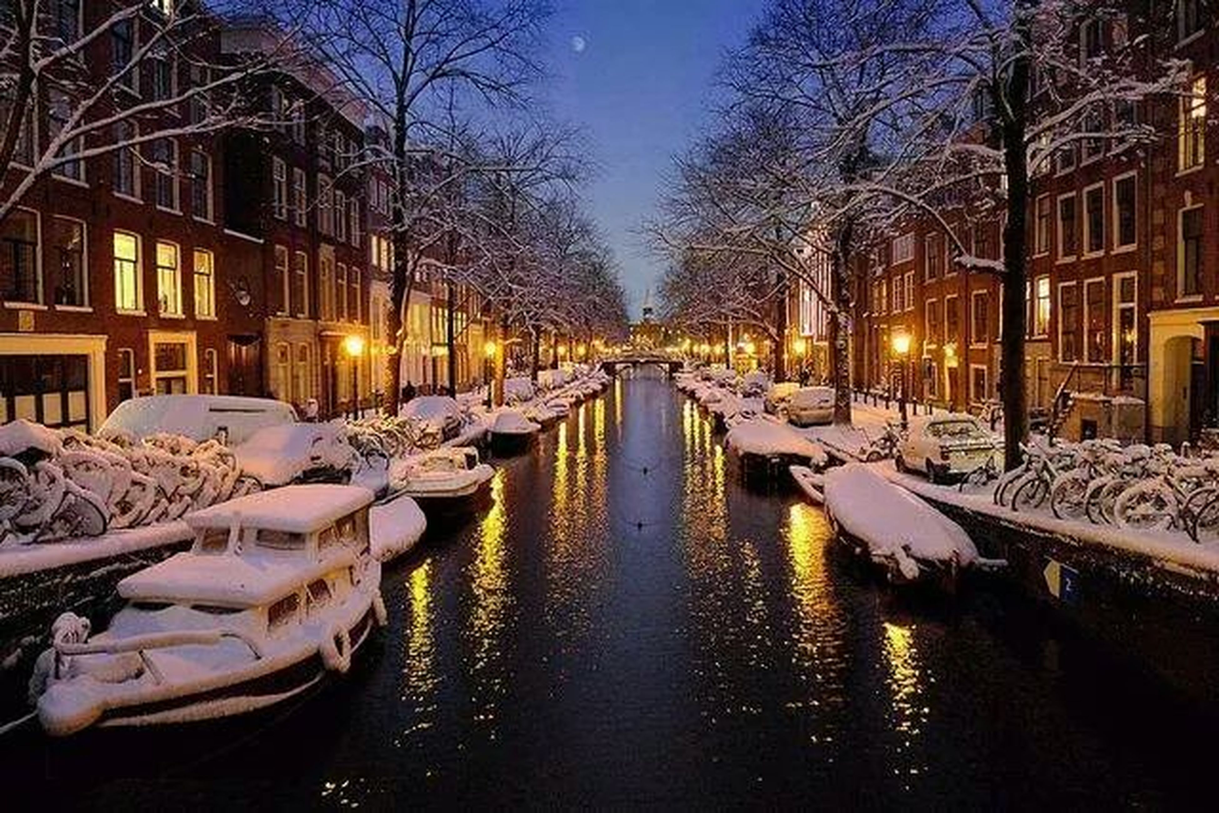 building exterior, built structure, architecture, canal, transportation, water, winter, bare tree, cold temperature, snow, city, mode of transport, illuminated, season, reflection, tree, street light, waterfront, moored, residential building