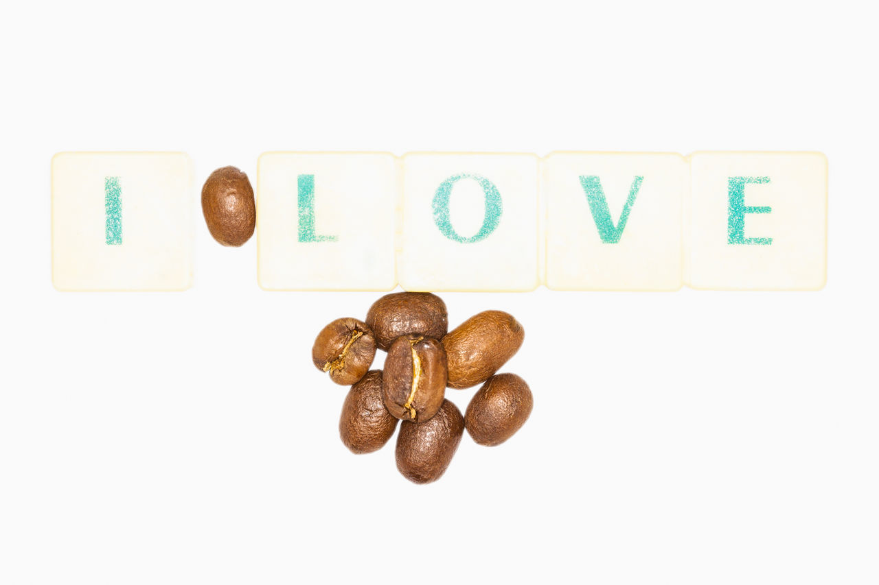 Inspirational Quote About Coffee Compose With Green Letters And Coffee Beans On A White Background Alphabet Christmas Close-up Coffee Communication Concept Currency Day Decorative I I Love Coffee Love Nature No People Number Party Quotes Raw Seed Spelling Studio Shot Text Valentine's Day  Vegan White Background