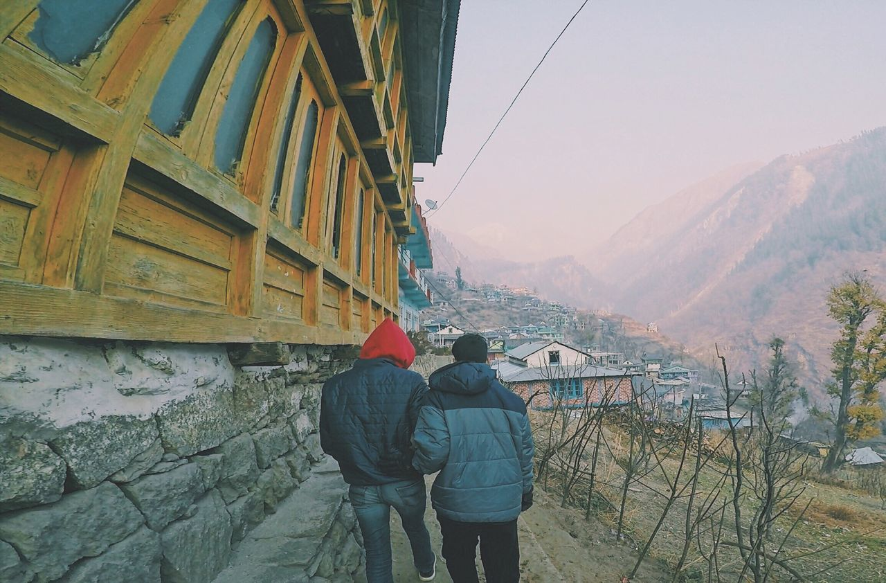 real people, rear view, two people, leisure activity, lifestyles, men, built structure, walking, day, togetherness, architecture, outdoors, women, nature, standing, mountain, warm clothing, building exterior, beauty in nature, sky, people