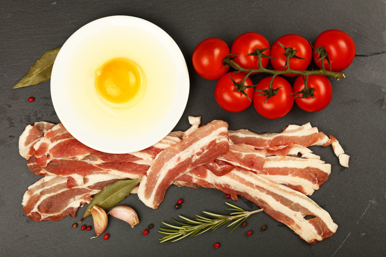 Cooking English breakfast, egg, bacon, red cherry tomatoes on black slate board, elevated top view Bacon Black Board Breakfast Cherry Tomatoes Close-up Cooking Directly Above Egg Elevated View English Breakfast Food Freshness Healthy Eating Meat Pork Rashers Raw Raw Food Red Rosemary Slate Spices Tomato Top View