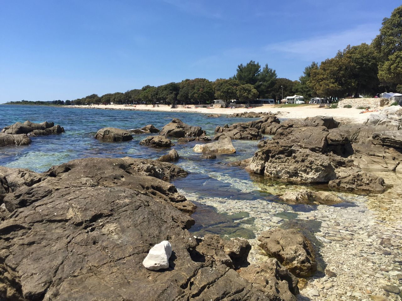nature, water, rock - object, sky, tranquility, tranquil scene, scenics, outdoors, beauty in nature, sunlight, beach, no people, day, landscape, sea, tree