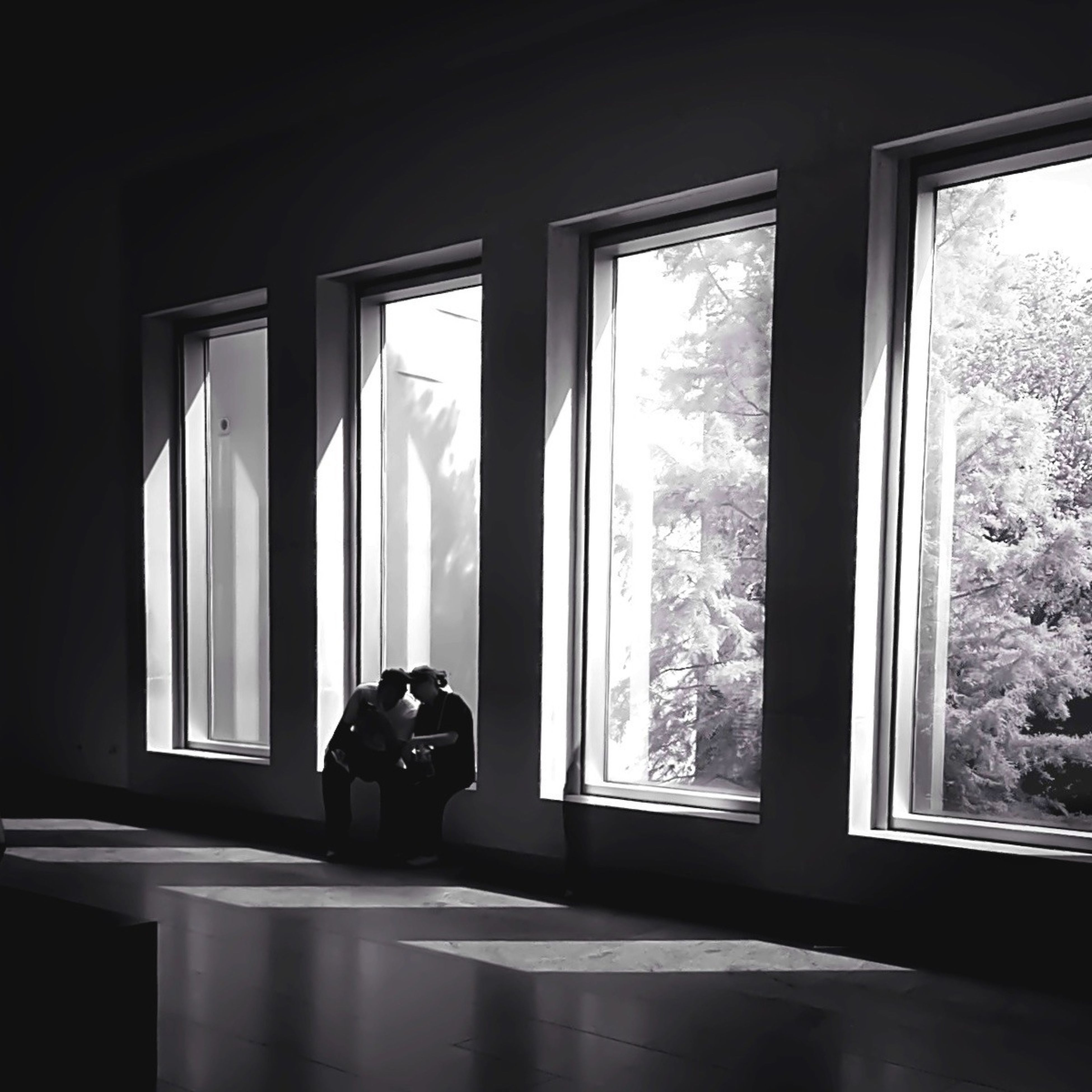 indoors, window, glass - material, transparent, lifestyles, looking through window, rear view, home interior, men, person, leisure activity, sitting, curtain, standing, glass, silhouette, day, full length