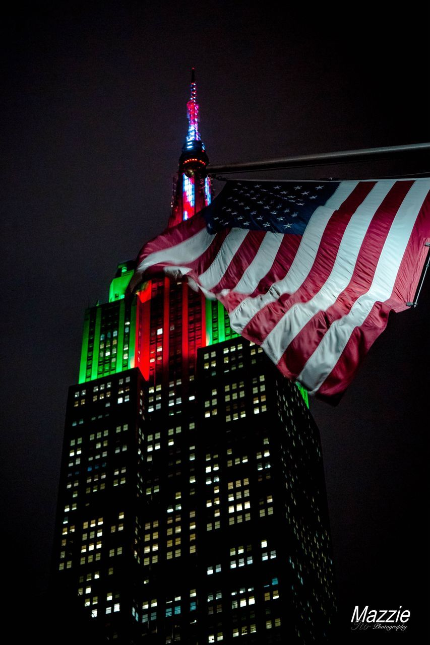 architecture, building exterior, flag, night, built structure, tall - high, low angle view, skyscraper, city, illuminated, no people, travel destinations, patriotism, modern, outdoors, clear sky, sky, stars and stripes