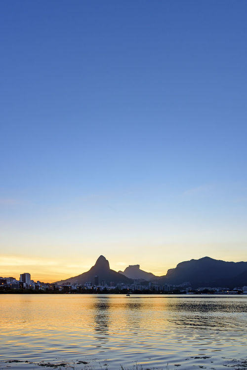 Image of the late afternoon at Lagoa Rodrigo de Freitas in Rio de Janeiro with its mountains, buildings and characteristic outline City Rio De Janeiro Skyline Travel Building Exterior Day Dusk Famous Place Hill Lake Landscape Mountain Nature No People Orange Color Outdoors Refletction Rodrigo De Freitas Lagoon Scenics Sky Summer Sunset Tropical Urban Water