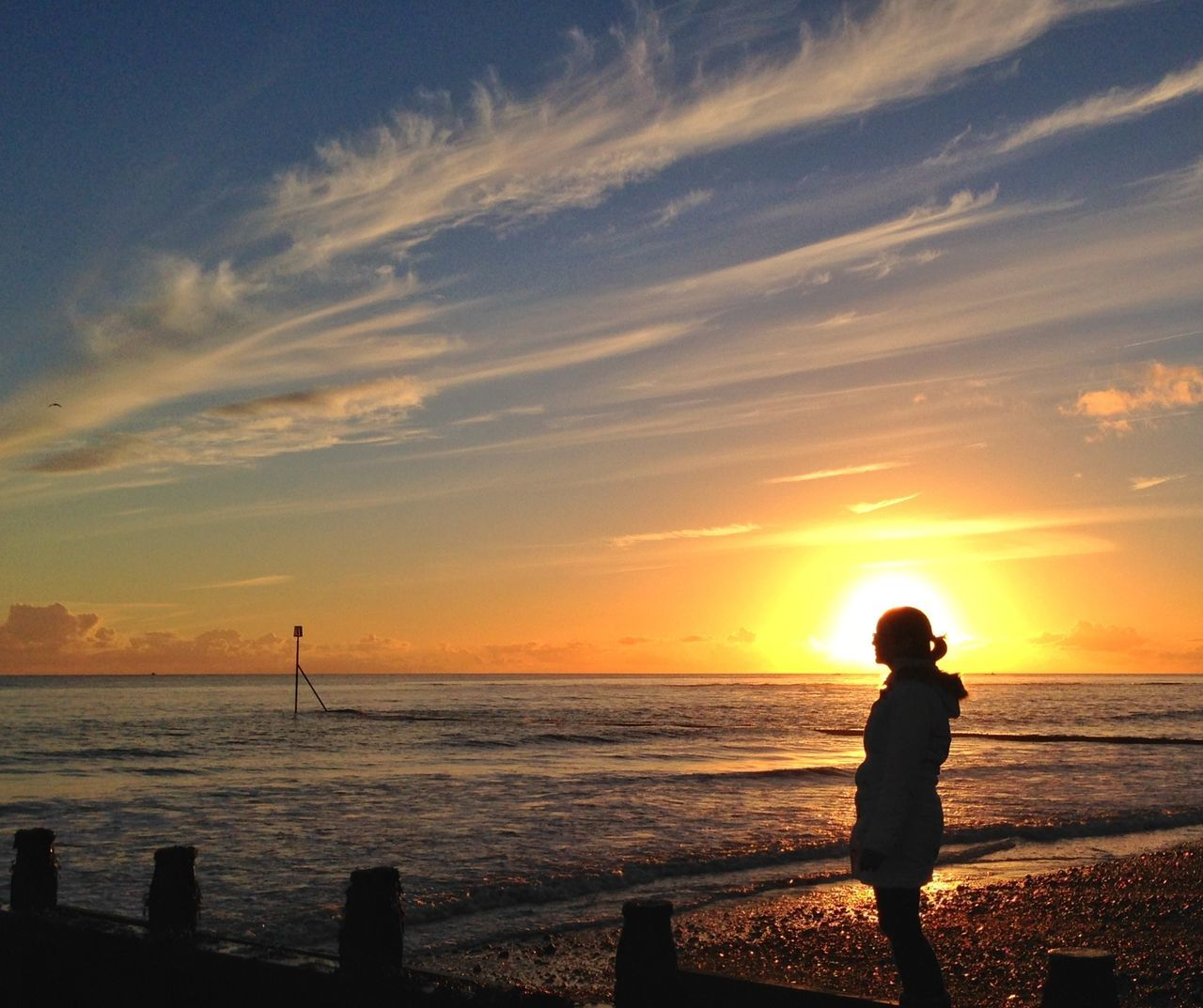 Silhouette Woman Overlooking Calm Sea At Sunset
