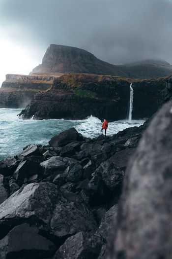 Faroe Islands Faroe Islands Scene Adventure Beauty In Nature Cliff Faroe Islands Leisure Activity Mountain Nature One Person Outdoors Real People Rock - Object Rock Formation Scenics Sea Standing Water Young Adult
