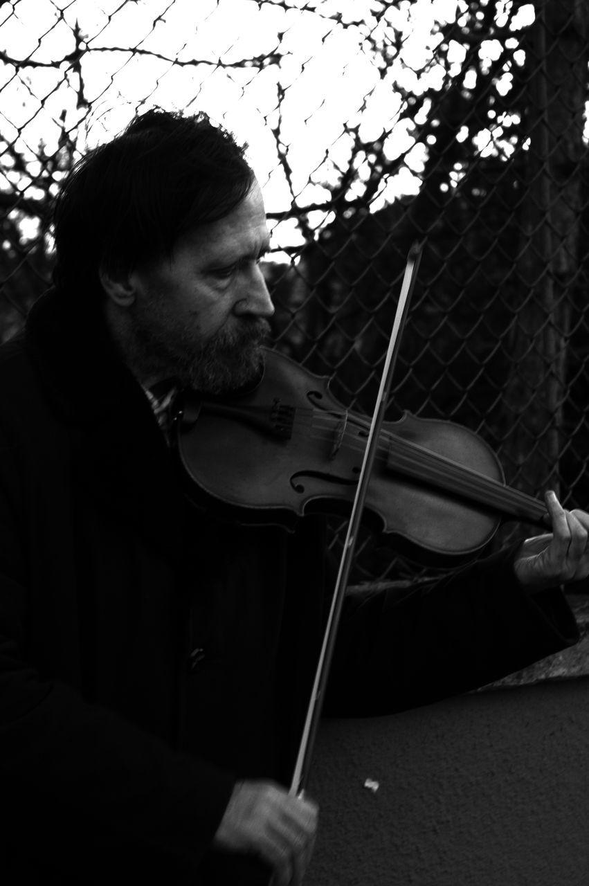 Mature Man Playing Violin At Dusk