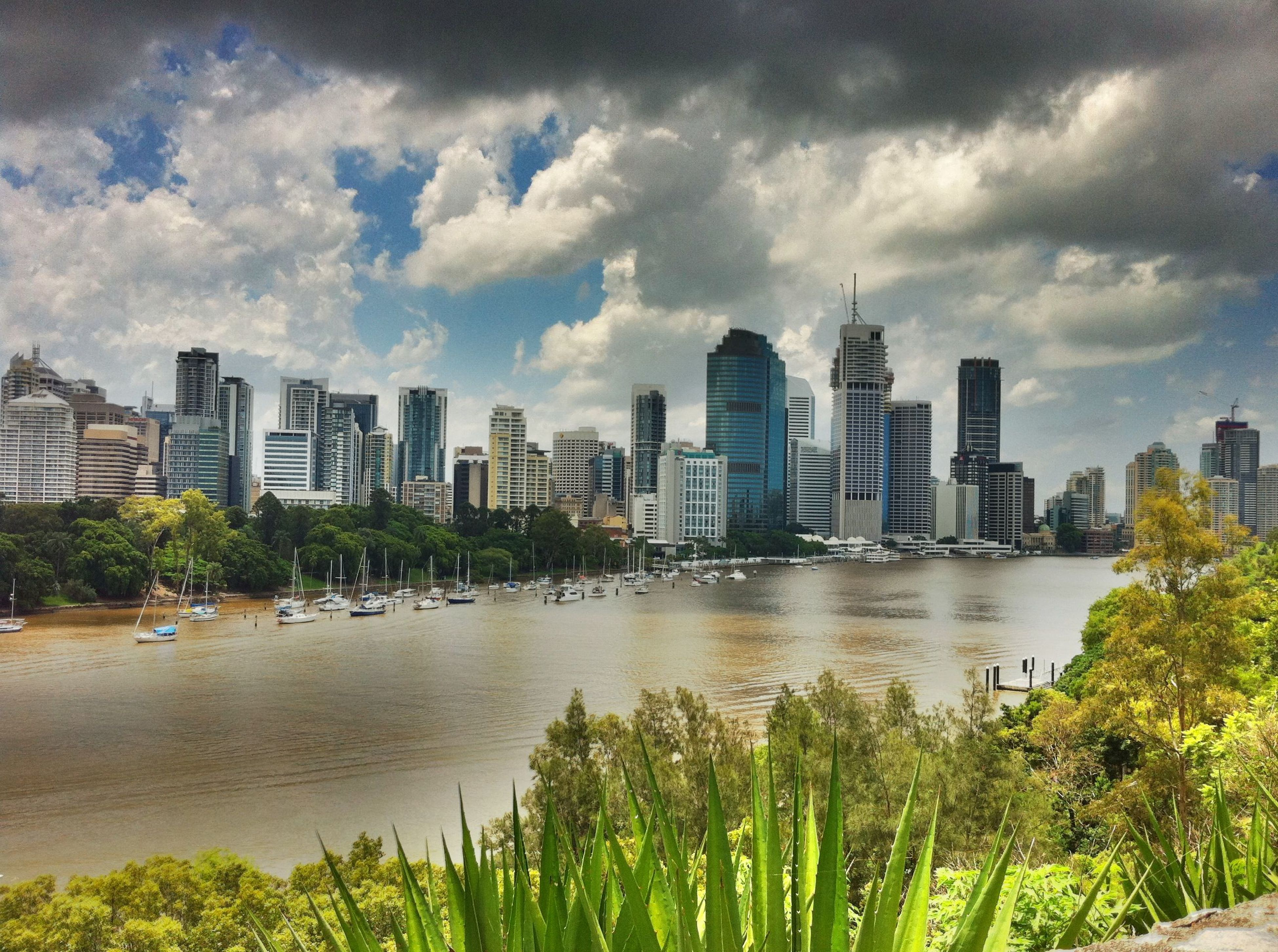 building exterior, architecture, built structure, city, sky, water, skyscraper, cityscape, cloud - sky, modern, river, tree, urban skyline, tall - high, cloudy, tower, growth, office building, cloud, city life