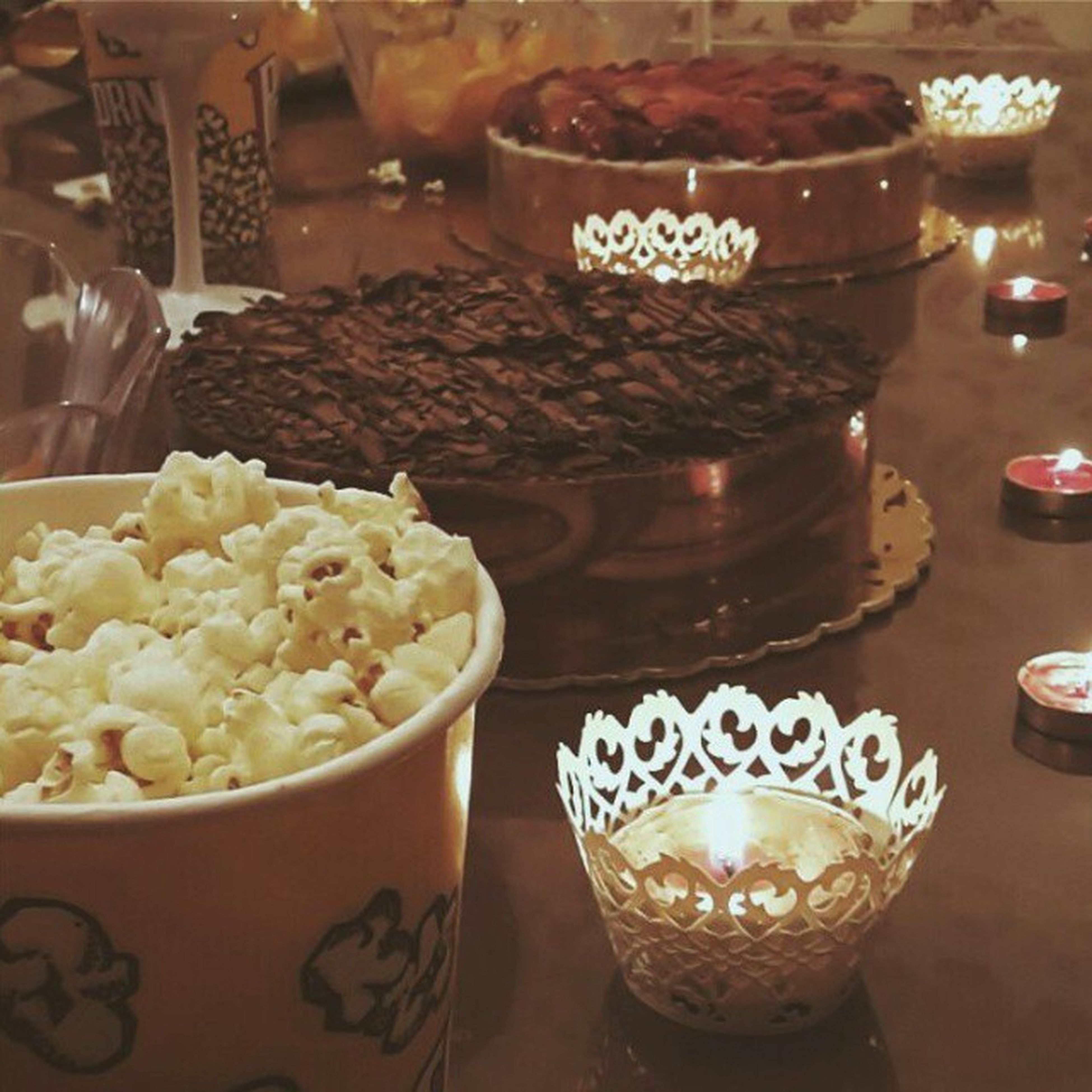 indoors, food and drink, candle, illuminated, table, flame, still life, food, freshness, sweet food, burning, lit, decoration, dessert, indulgence, fire - natural phenomenon, cake, restaurant, large group of objects, heat - temperature