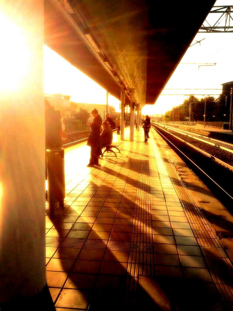 transportation, sunlight, real people, railroad station, railroad station platform, railroad track, public transportation, men, rail transportation, lifestyles, built structure, shadow, commuter, indoors, women, architecture, day, illuminated, city, people, adult