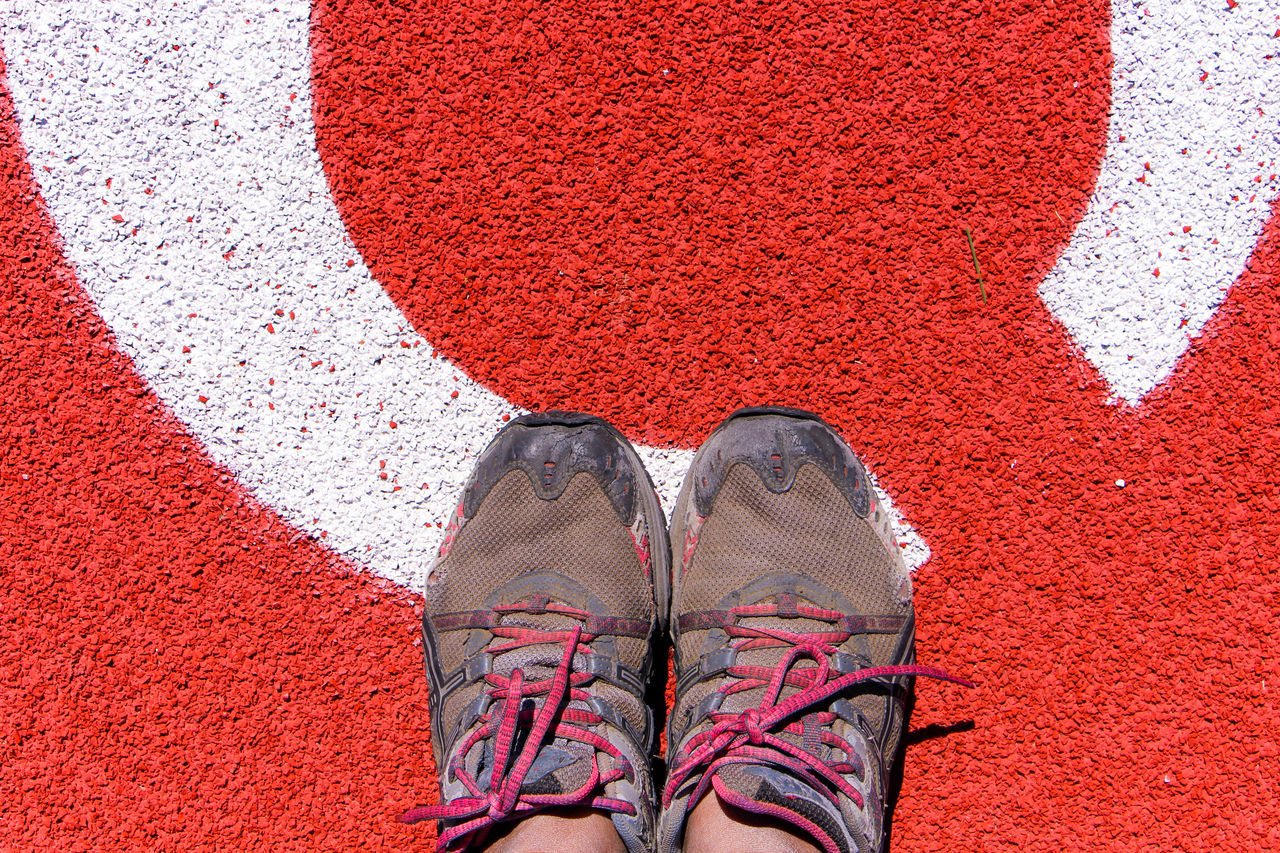 Low Section Of Person Wearing Shoes Standing On Playing Field