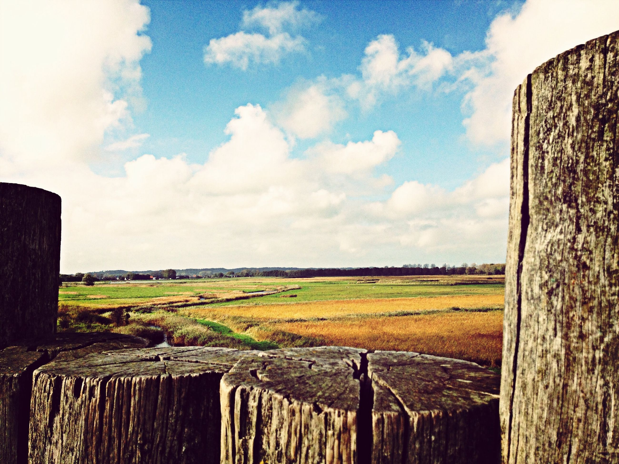 sky, cloud - sky, fence, grass, field, landscape, tranquility, cloud, tranquil scene, water, built structure, building exterior, scenics, wooden post, rural scene, nature, architecture, beauty in nature, day, cloudy