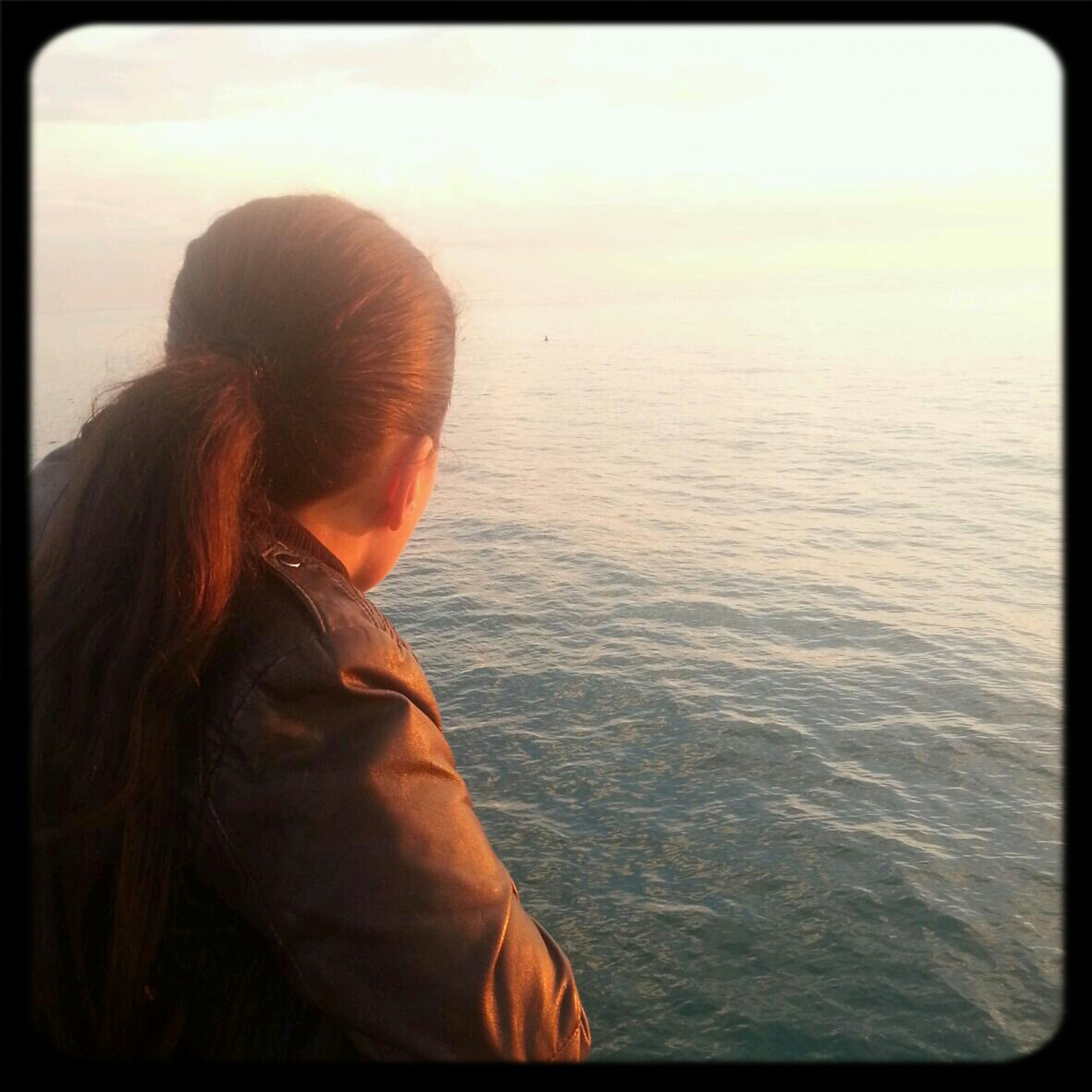 transfer print, auto post production filter, sea, water, lifestyles, rear view, leisure activity, sunset, long hair, headshot, sky, horizon over water, person, scenics, tranquil scene, beauty in nature, tranquility, waist up