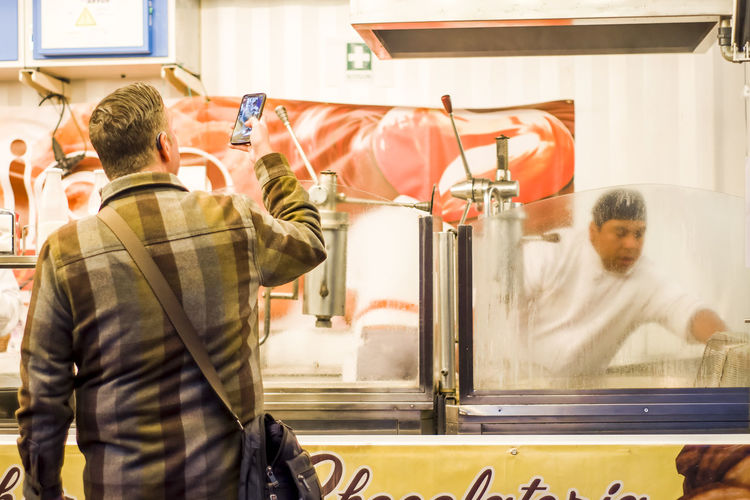 Man taking a photo of a Churros maker at a stall in Opera Madrid Spain. Churro Churros City City Life Steam Tourist Winter Candid Candid Photography Editorial  Indoors  Maker Men Mobile Photography Occupation People Real People Stall Standing Street Street Food Tourism Uniform Working