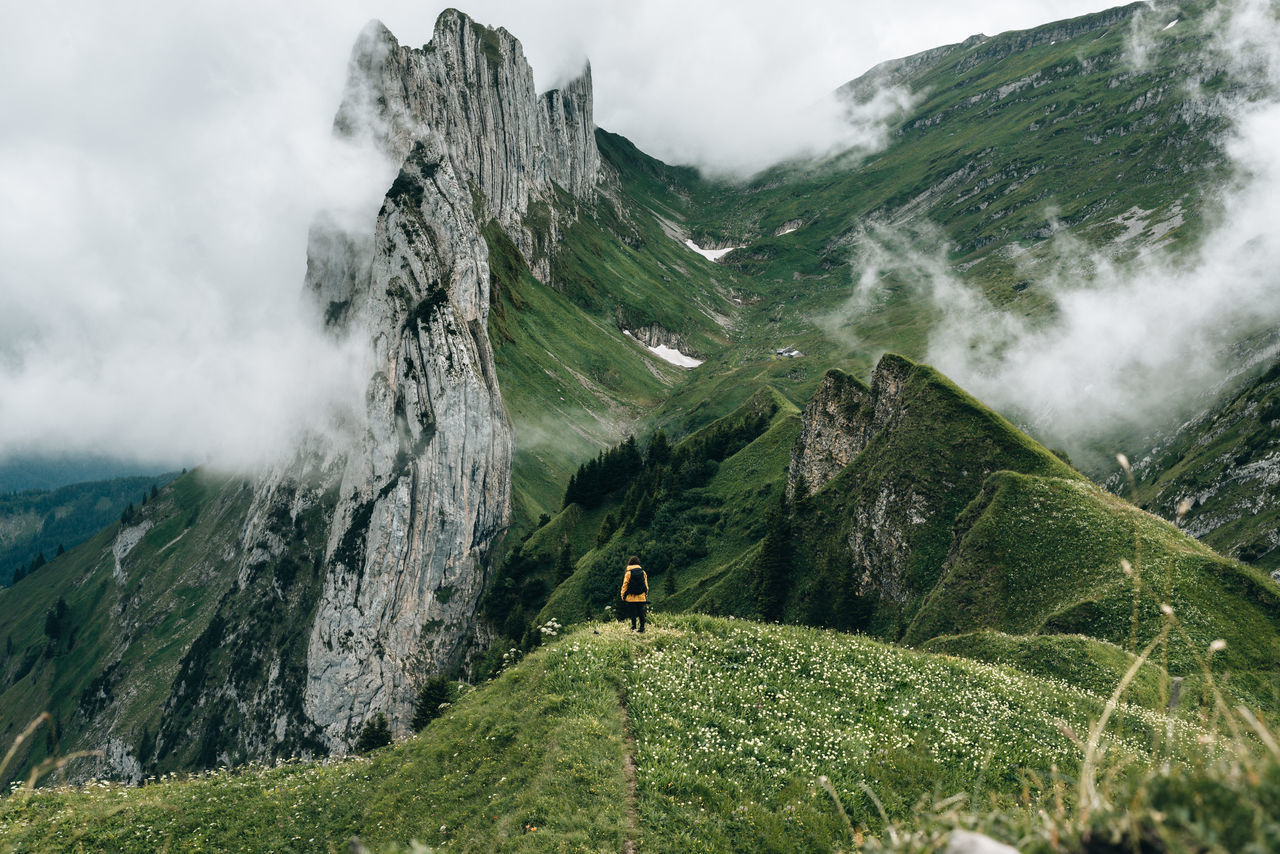 Person standing in front of a majestic mountain range in switzerland