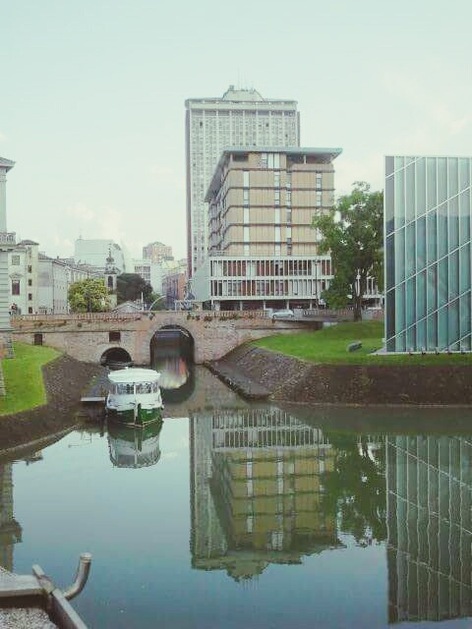 reflection, architecture, building exterior, built structure, water, city, outdoors, sky, day, modern, waterfront, skyscraper, no people, tree, puddle