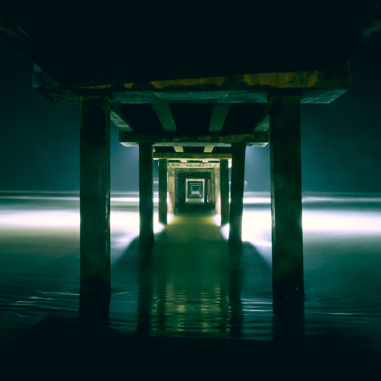 underneath, bridge - man made structure, architectural column, built structure, architecture, below, indoors, water, no people, illuminated, night