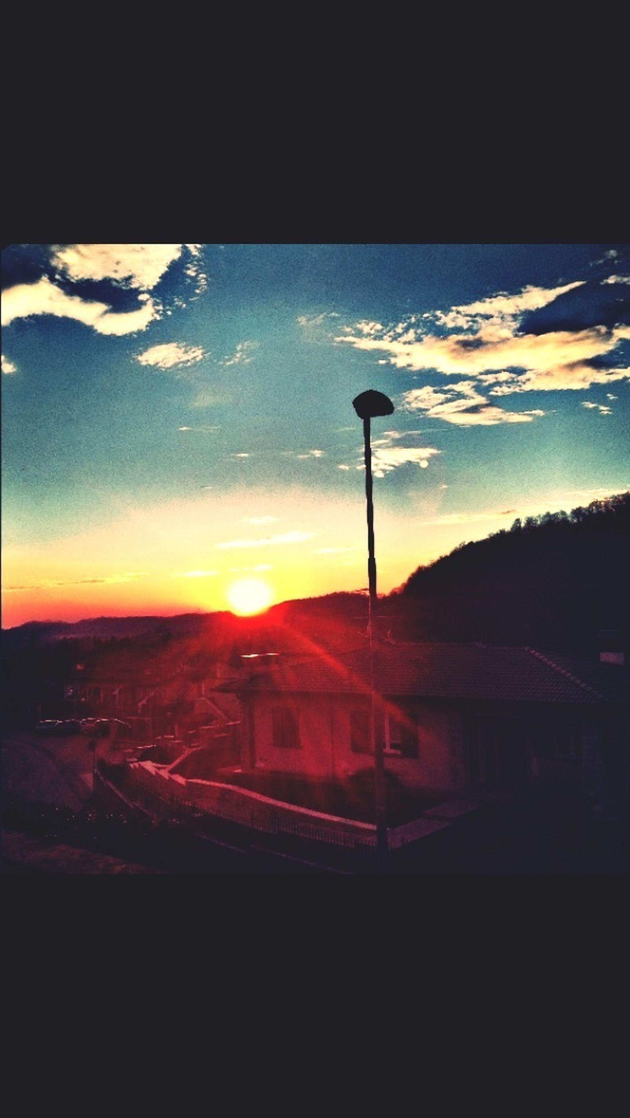 sunset, sky, transportation, silhouette, cloud - sky, sun, built structure, orange color, architecture, street light, dark, car, building exterior, mode of transport, dusk, sunlight, auto post production filter, landscape, land vehicle, cloud