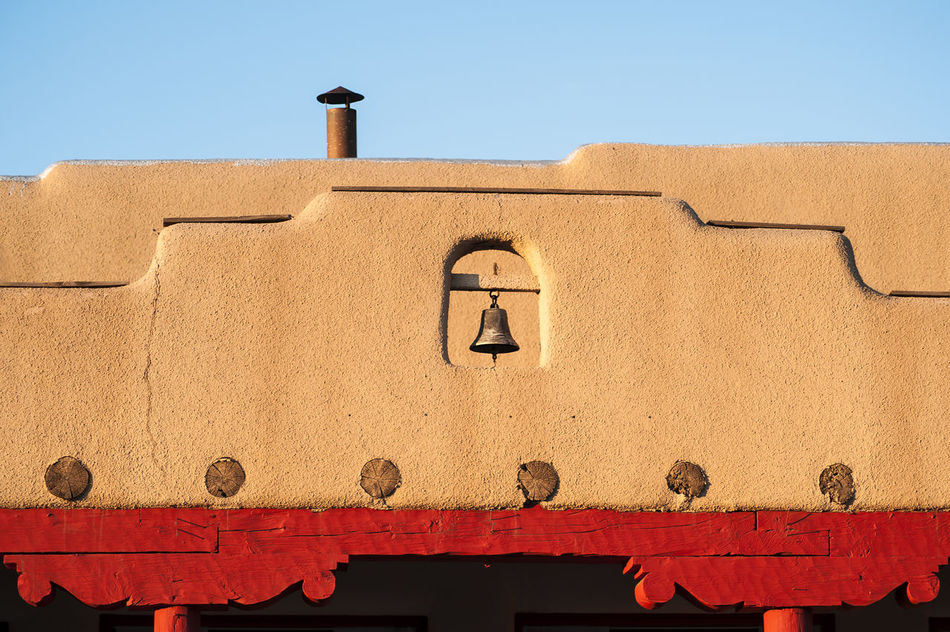 Adobe structure in New Mexico Adobe Arch Architecture Bell Blue Brown Building Exterior Built Structure Chimney Clear Sky Day Exterior Façade High Section History Low Angle View New Mexico No People Outdoors Red Roof Sky Town Window
