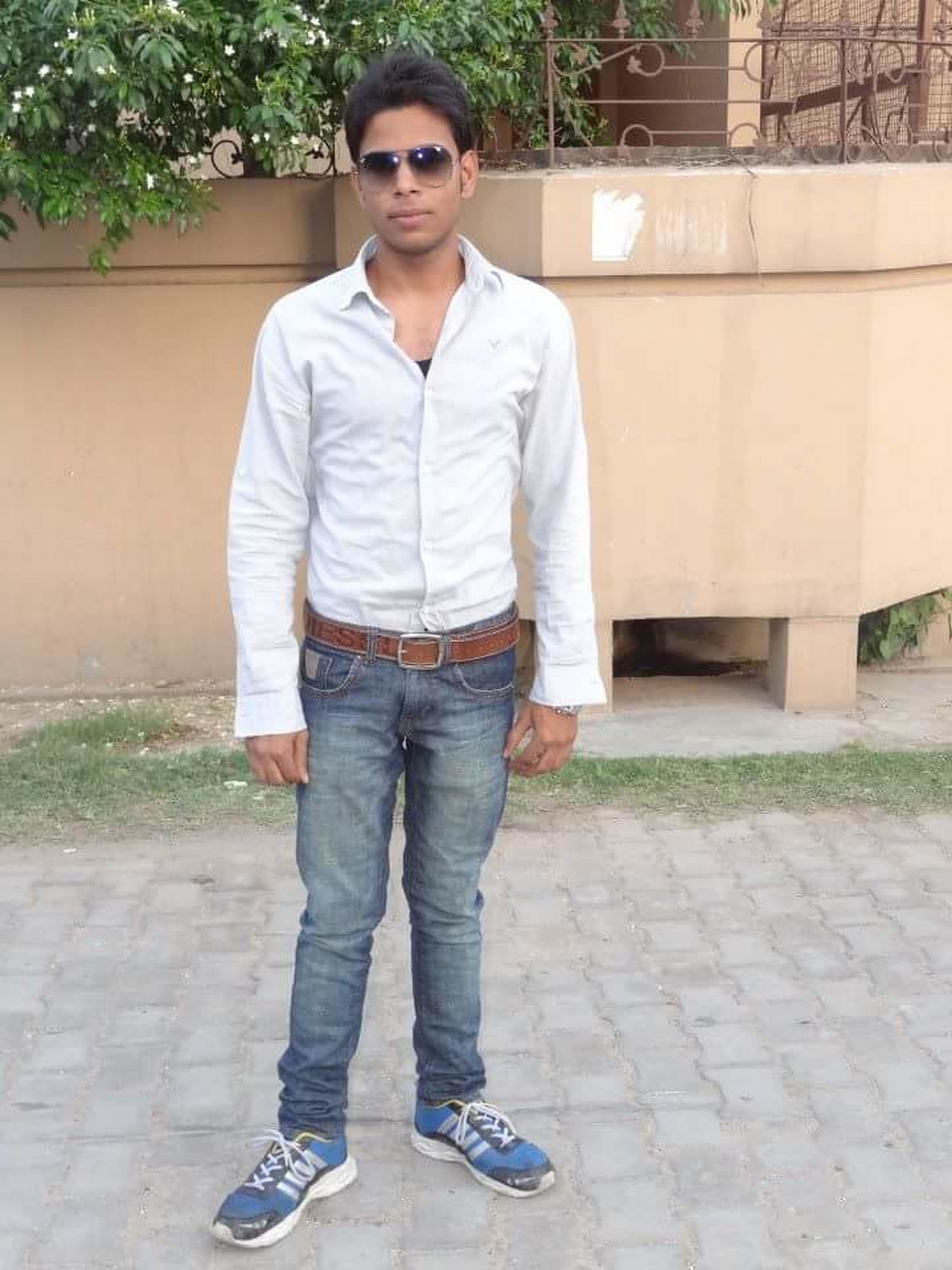 looking at camera, casual clothing, portrait, person, front view, lifestyles, standing, young adult, full length, leisure activity, smiling, young men, jeans, three quarter length, hands in pockets, sunglasses, happiness