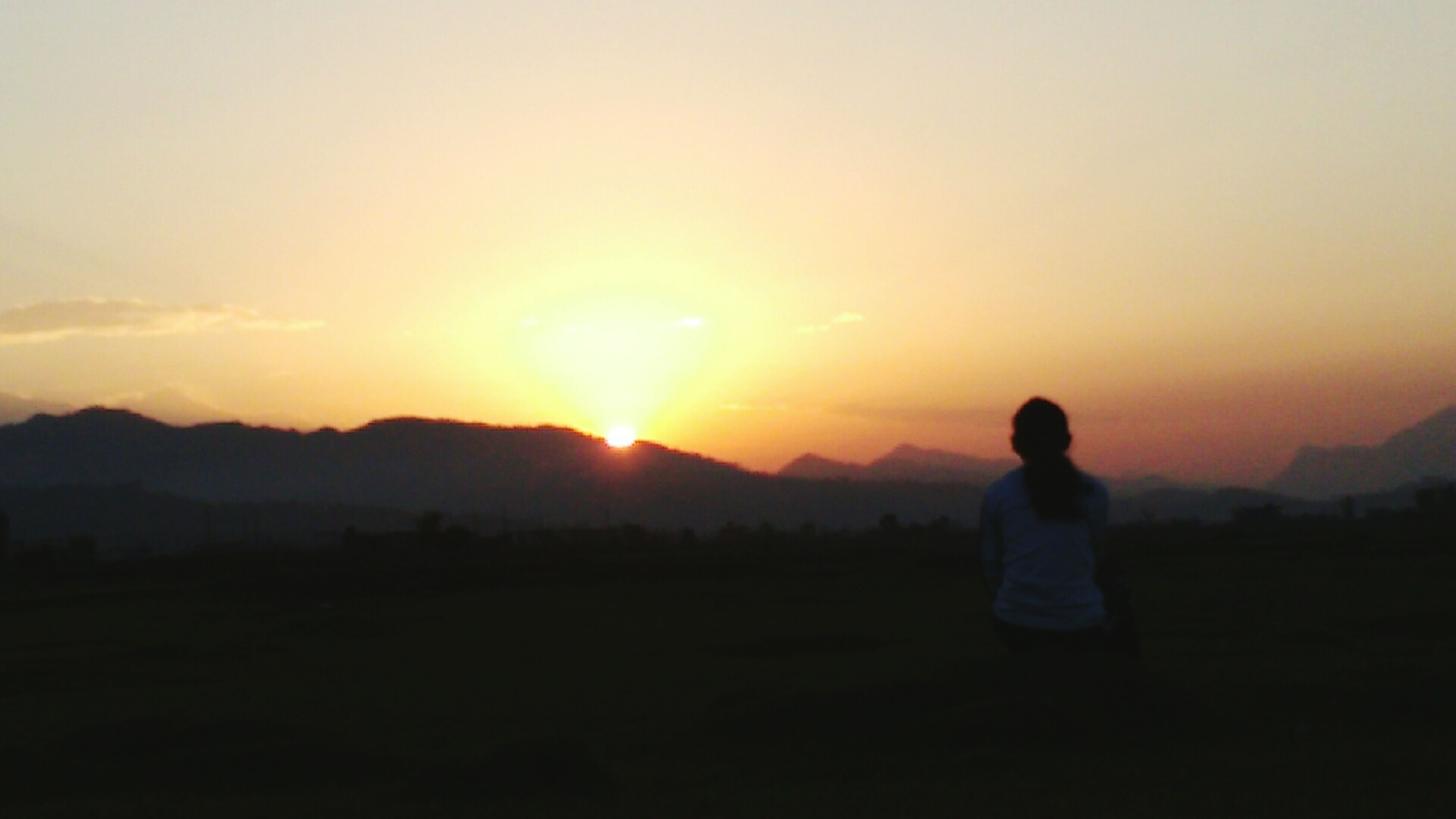 sunset, silhouette, scenics, sun, tranquil scene, beauty in nature, landscape, tranquility, orange color, sky, mountain, nature, lifestyles, standing, copy space, idyllic, leisure activity, rear view
