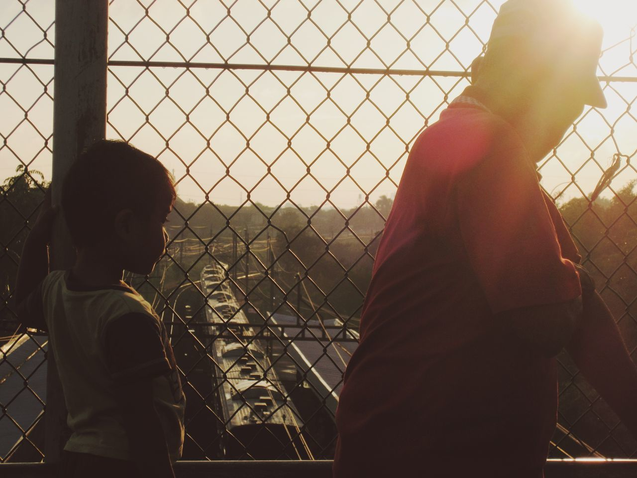 chainlink fence, real people, two people, togetherness, standing, day, outdoors, childhood, city, sky, close-up, friendship, people