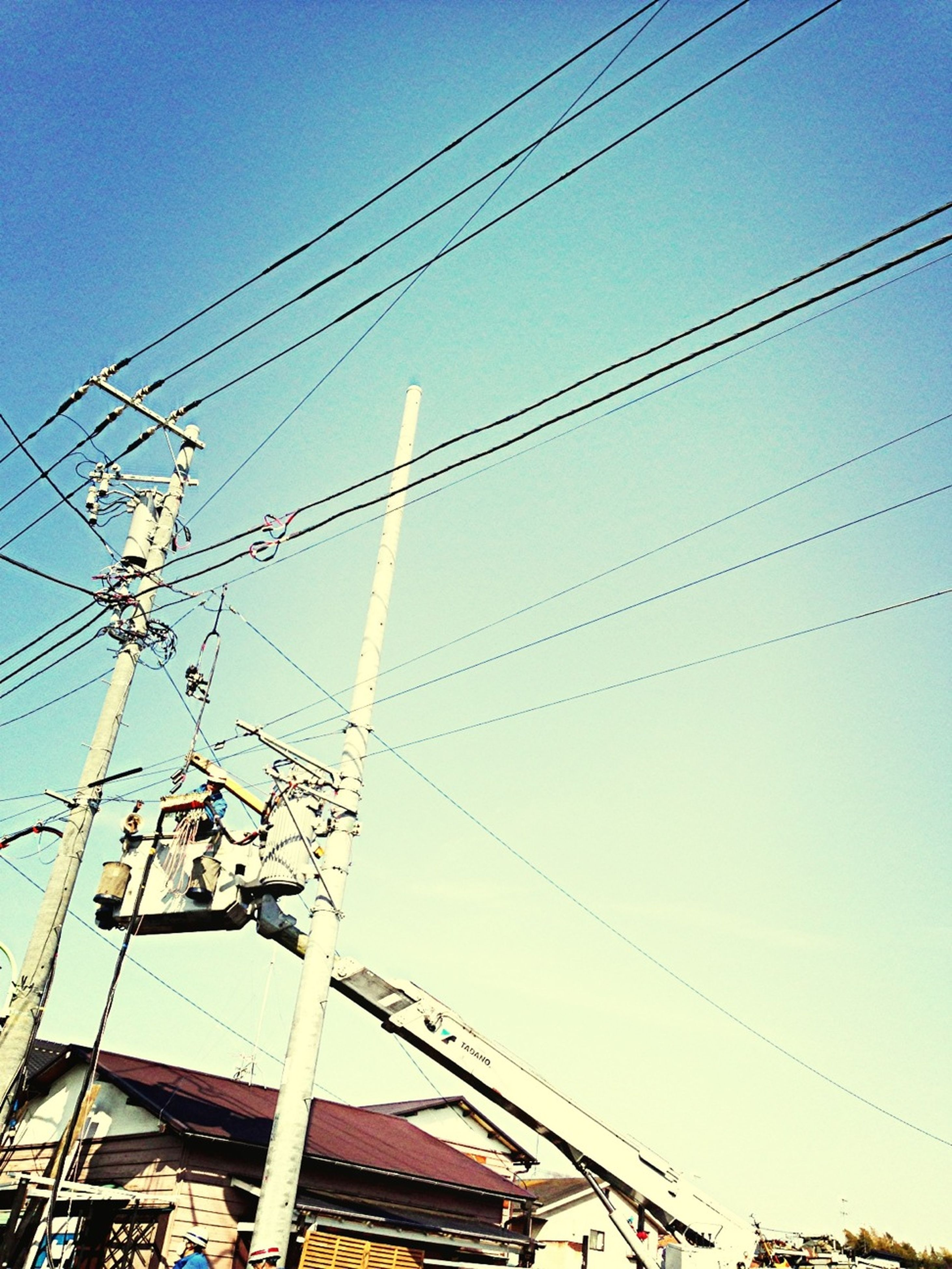 low angle view, power line, electricity, power supply, electricity pylon, cable, connection, fuel and power generation, technology, clear sky, power cable, sky, complexity, blue, lighting equipment, outdoors, built structure, day, no people, wire