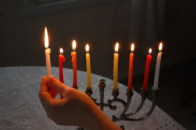 Burning Candle Candlelight Close-up Cropped Fire - Natural Phenomenon Flame Focus On Foreground Glowing Hand Hannukah Heat - Temperature Holding Holiday Human Finger Illuminated Indoors  Judaica Judaism Menorah Person Relegion Womenshand