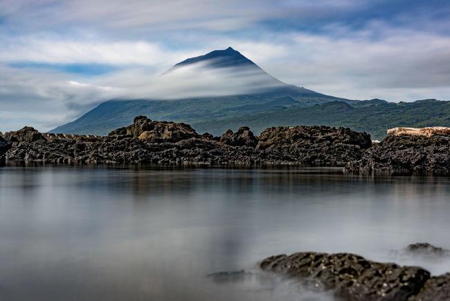 Pico volcano shows it's pointy peak, surrounded by Atlantic clouds Beauty In Nature Idyllic Landscape Long Exposure Majestic Mountain Mountain Range Nature No People Non-urban Scene Outdoors Photooftheday Pico Picoftheday Portugal Reflection Reflection Rock Formation Scenics Sky Tranquil Scene Volcano Water Waterfront Weather