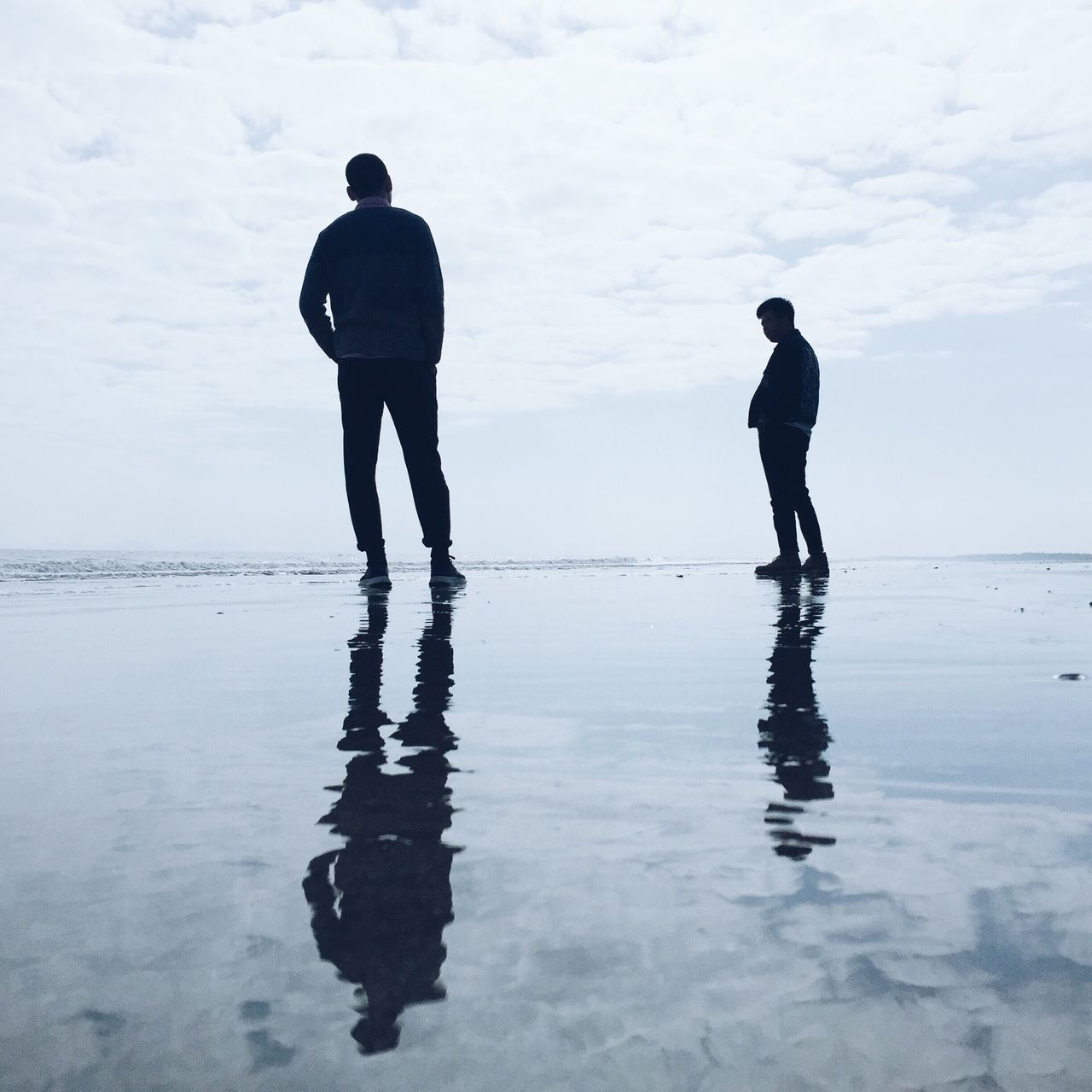 sea, water, silhouette, walking, two people, real people, nature, reflection, beach, leisure activity, rear view, men, beauty in nature, full length, lifestyles, outdoors, standing, vacations, waterfront, scenics, horizon over water, sky, day, ankle deep in water, people