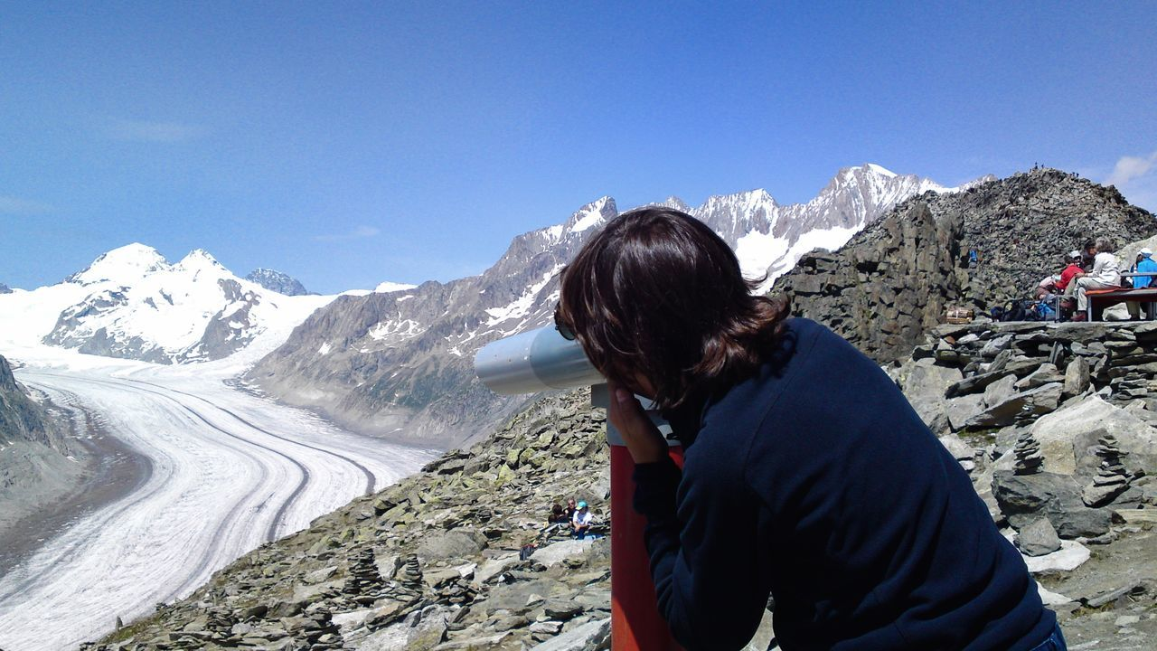 Boy Looking Though Telescope At Aletsch Glacier