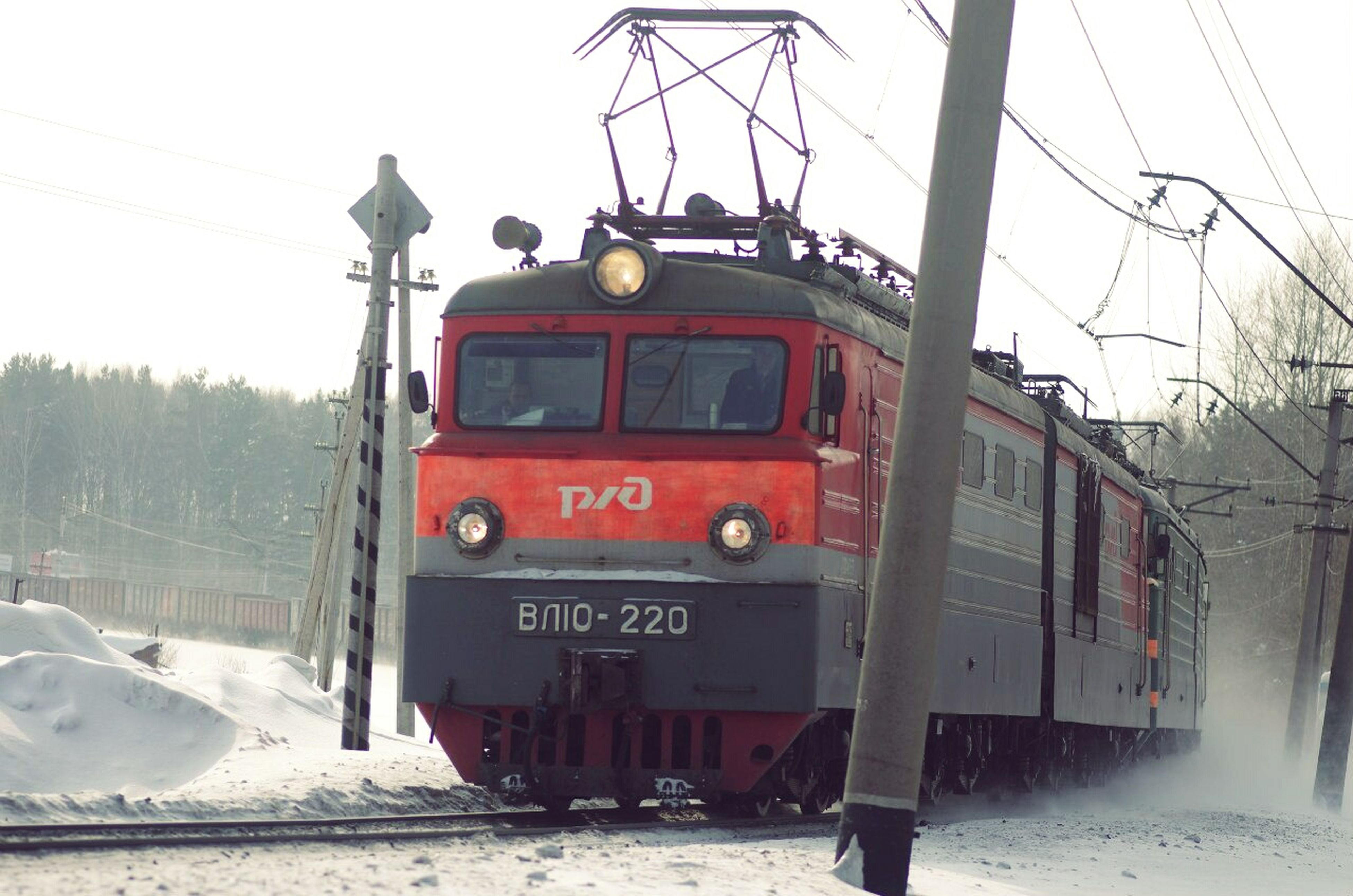 snow, cold temperature, transportation, winter, mode of transport, power line, season, railroad track, electricity pylon, land vehicle, weather, cable, electricity, building exterior, rail transportation, train - vehicle, public transportation, power supply, clear sky, built structure
