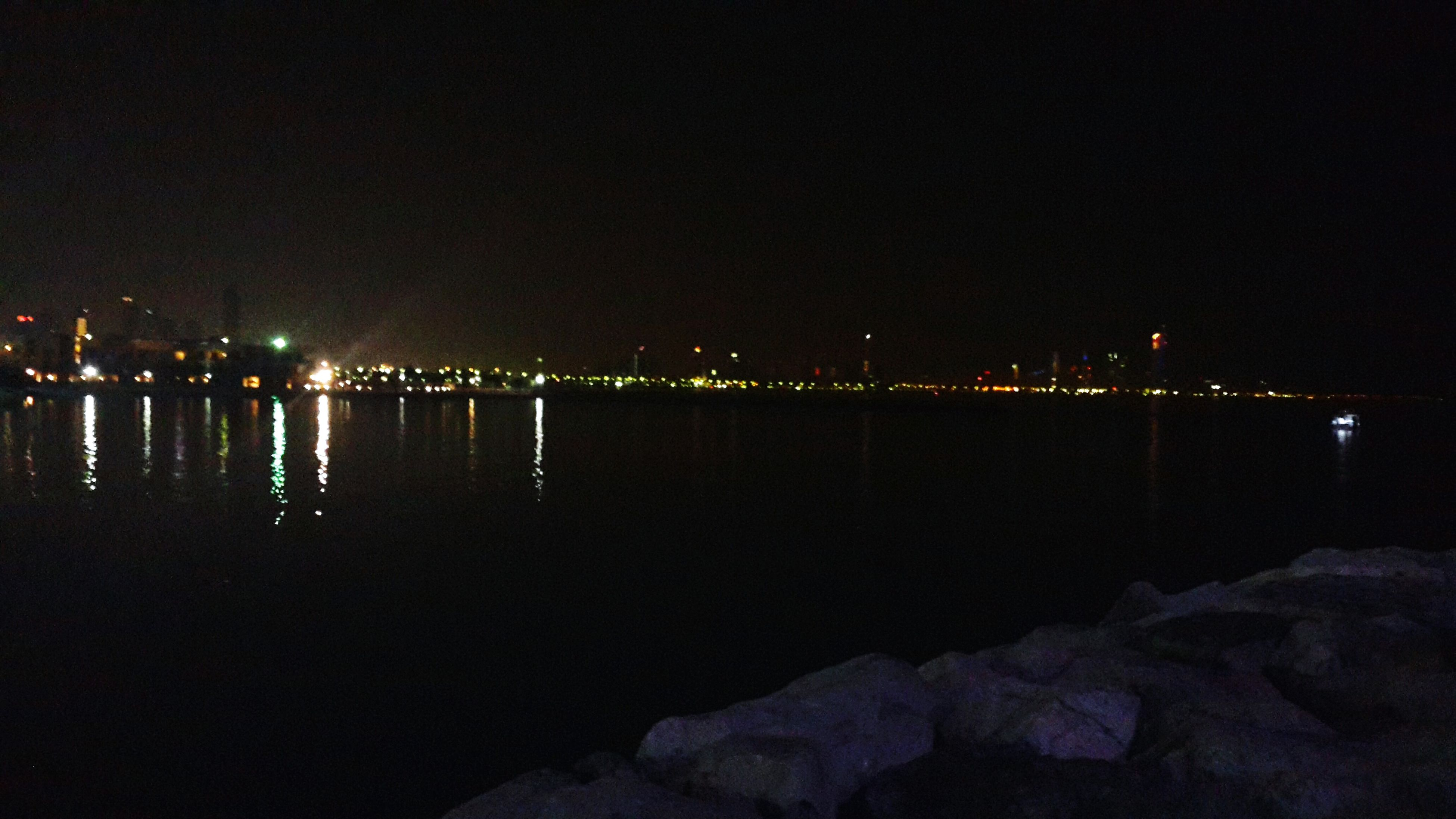 night, illuminated, water, reflection, sea, tranquil scene, copy space, clear sky, waterfront, tranquility, scenics, river, built structure, architecture, lake, beauty in nature, nature, lighting equipment, standing water, sky