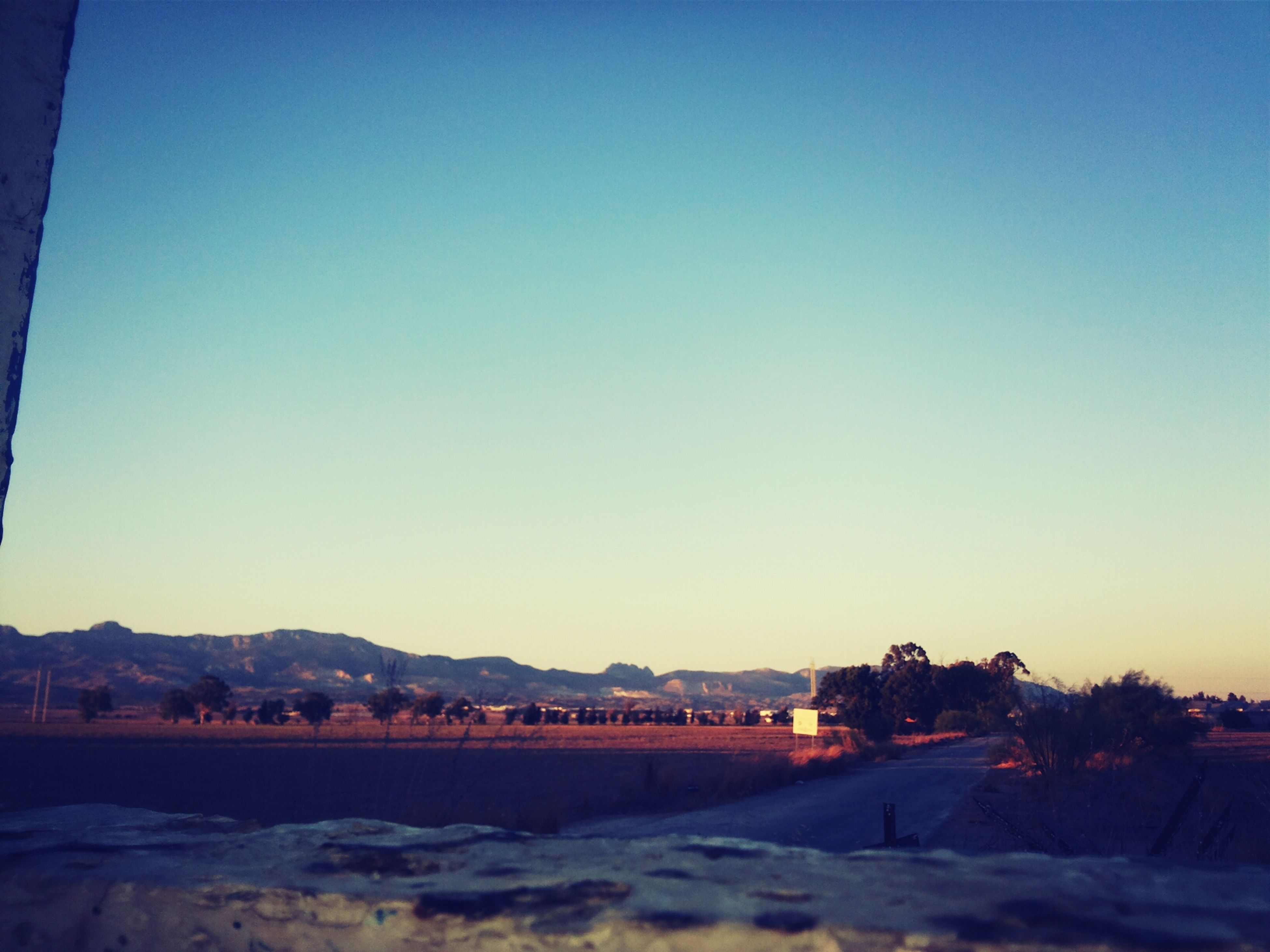 clear sky, copy space, blue, road, landscape, tranquil scene, tranquility, mountain, built structure, nature, scenics, dusk, sand, outdoors, building exterior, beauty in nature, architecture, tree, sunset, no people