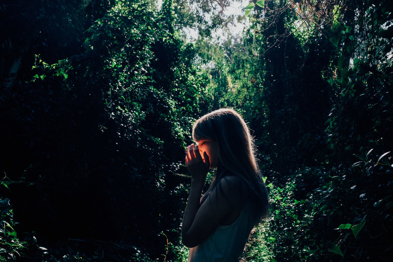 Side View Of Young Woman Against Trees In Forest