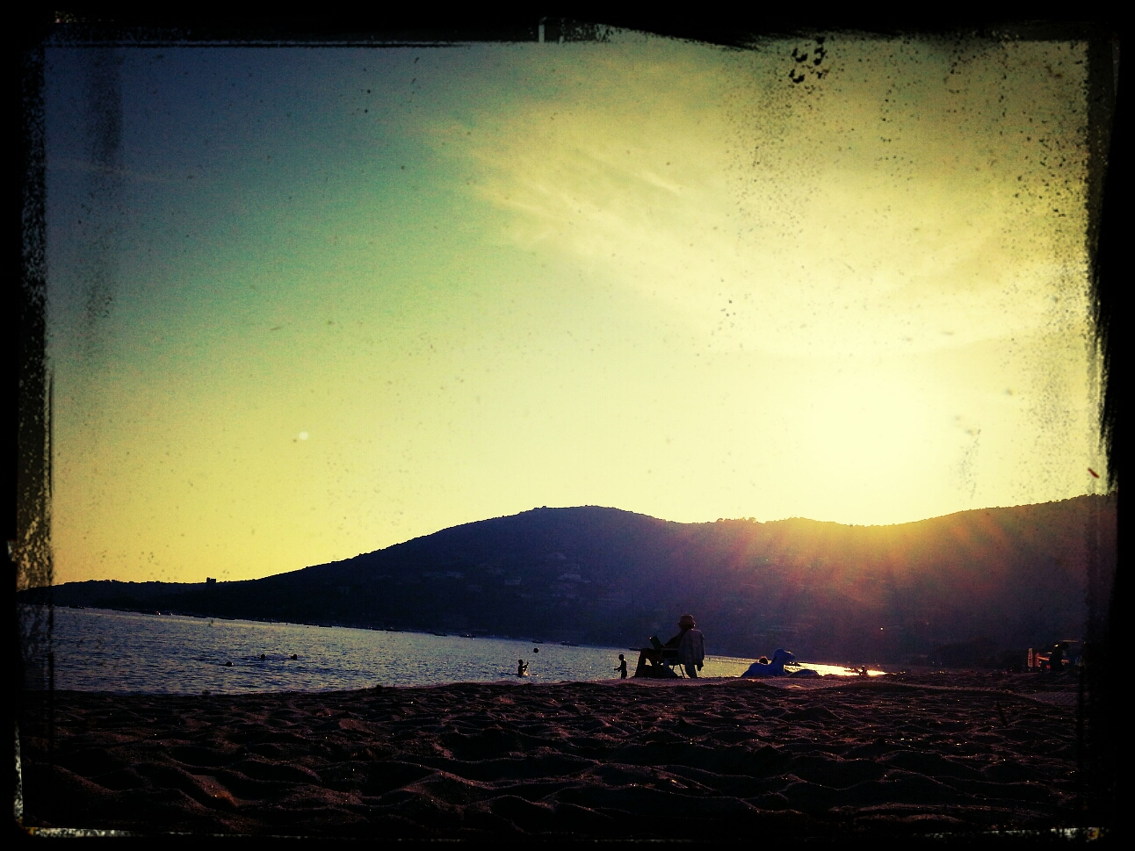 transfer print, auto post production filter, water, scenics, sunset, sun, tranquil scene, mountain, silhouette, tranquility, sky, beauty in nature, beach, nature, sea, leisure activity, sunlight, lifestyles, large group of people