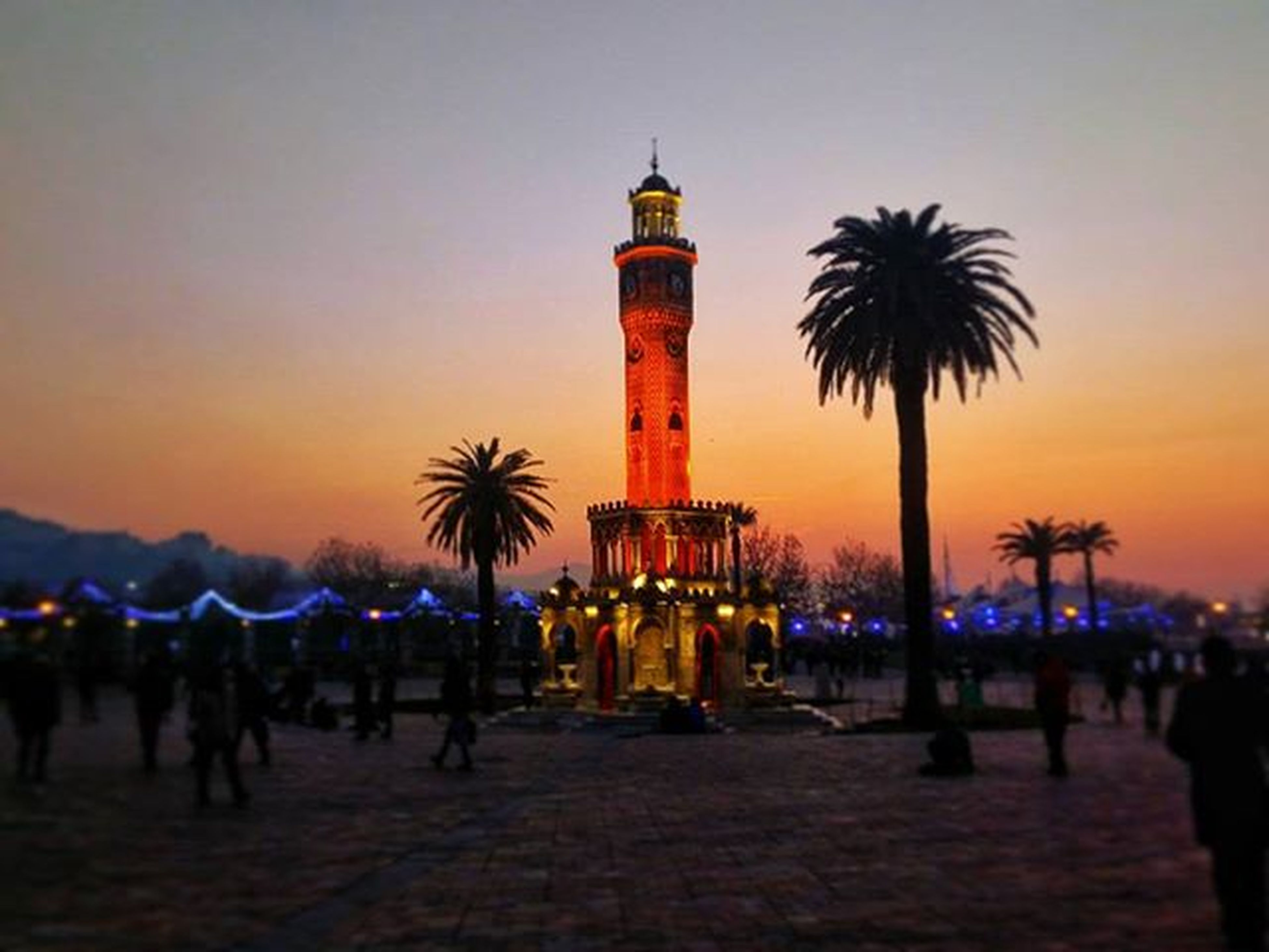 sunset, silhouette, built structure, architecture, building exterior, palm tree, clear sky, famous place, tourism, travel destinations, dusk, orange color, tower, sky, religion, tall - high, travel, incidental people, guidance, tree