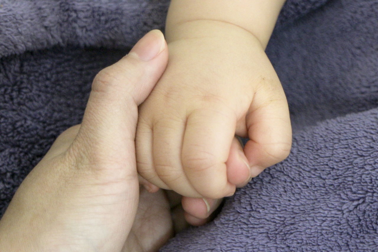 Close-Up Of Baby Holding Mother Hand