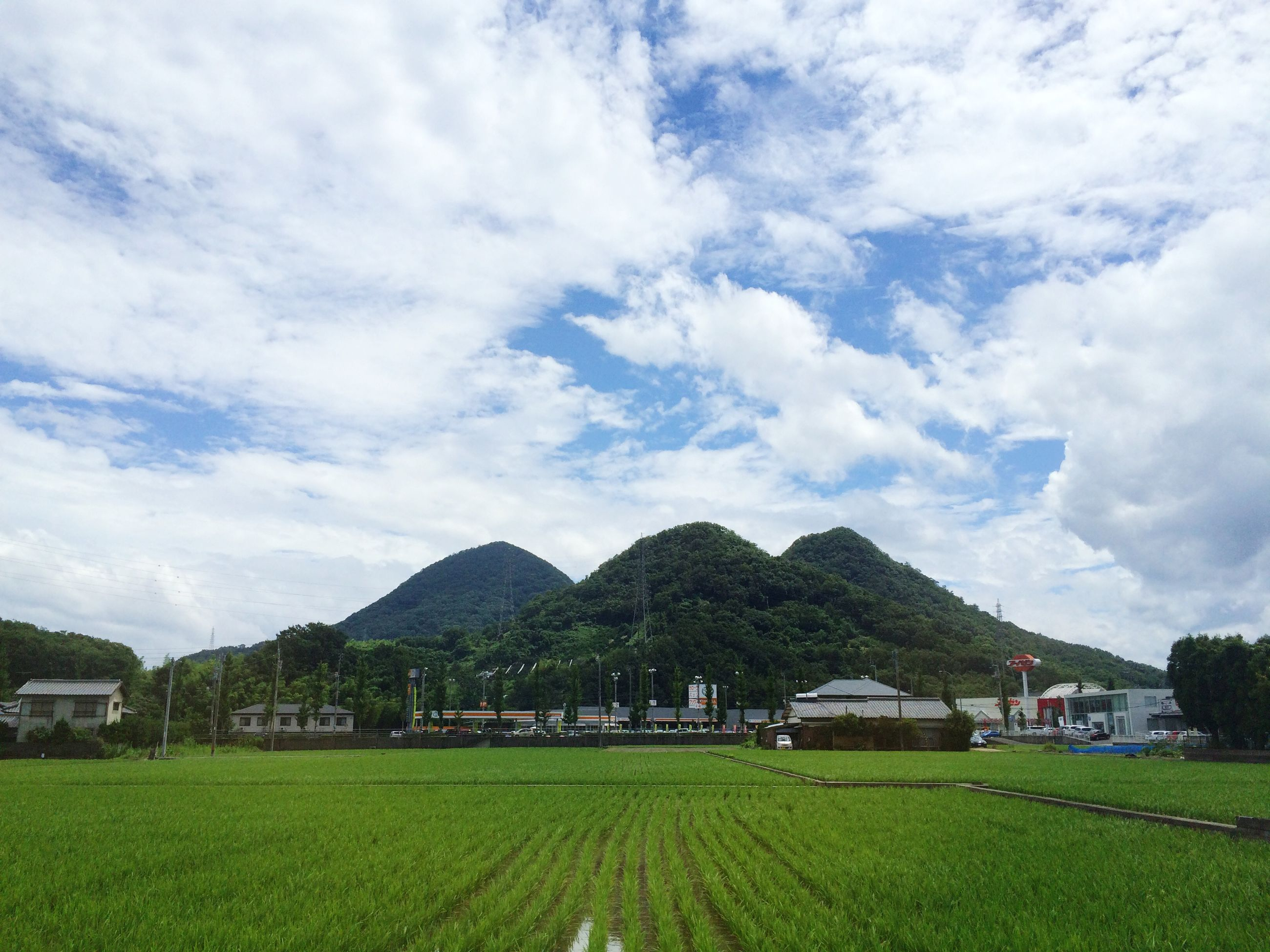 sky, landscape, grass, agriculture, field, building exterior, rural scene, mountain, architecture, cloud - sky, tranquil scene, built structure, farm, cloud, house, scenics, village, tranquility, beauty in nature, green color
