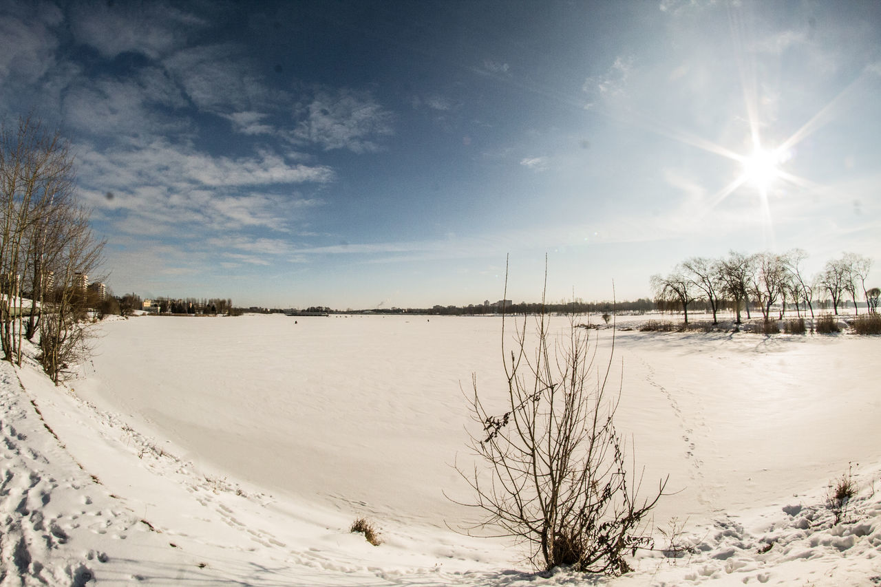 cold temperature, snow, winter, nature, tranquil scene, tranquility, beauty in nature, scenics, sun, sky, weather, non-urban scene, outdoors, bare tree, no people, landscape, tree, frozen, sunlight, lake, water, day