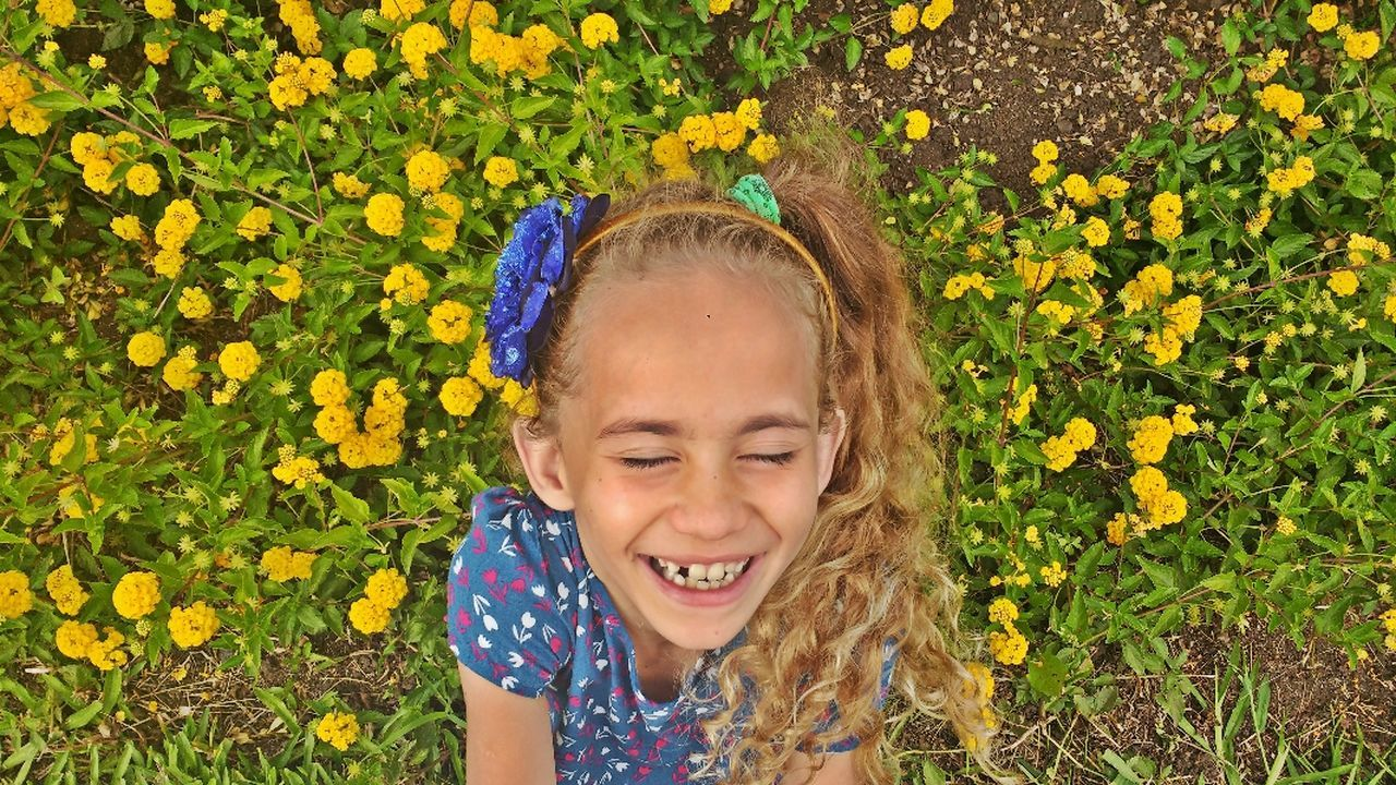 flower, yellow, eyes closed, day, outdoors, childhood, front view, one person, happiness, children only, smiling, child, nature, freshness, fun, one girl only, girls, leisure activity, plant, blond hair, summer, headshot, close-up, growth, fragility, beauty in nature, real people, grass, people, flower head