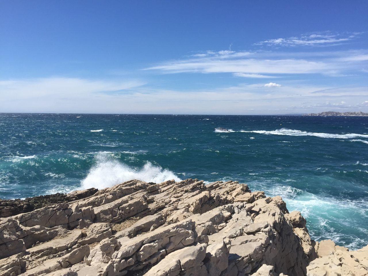 Scenic View Of Sea Waves Splashing Towards Rock Against Sky