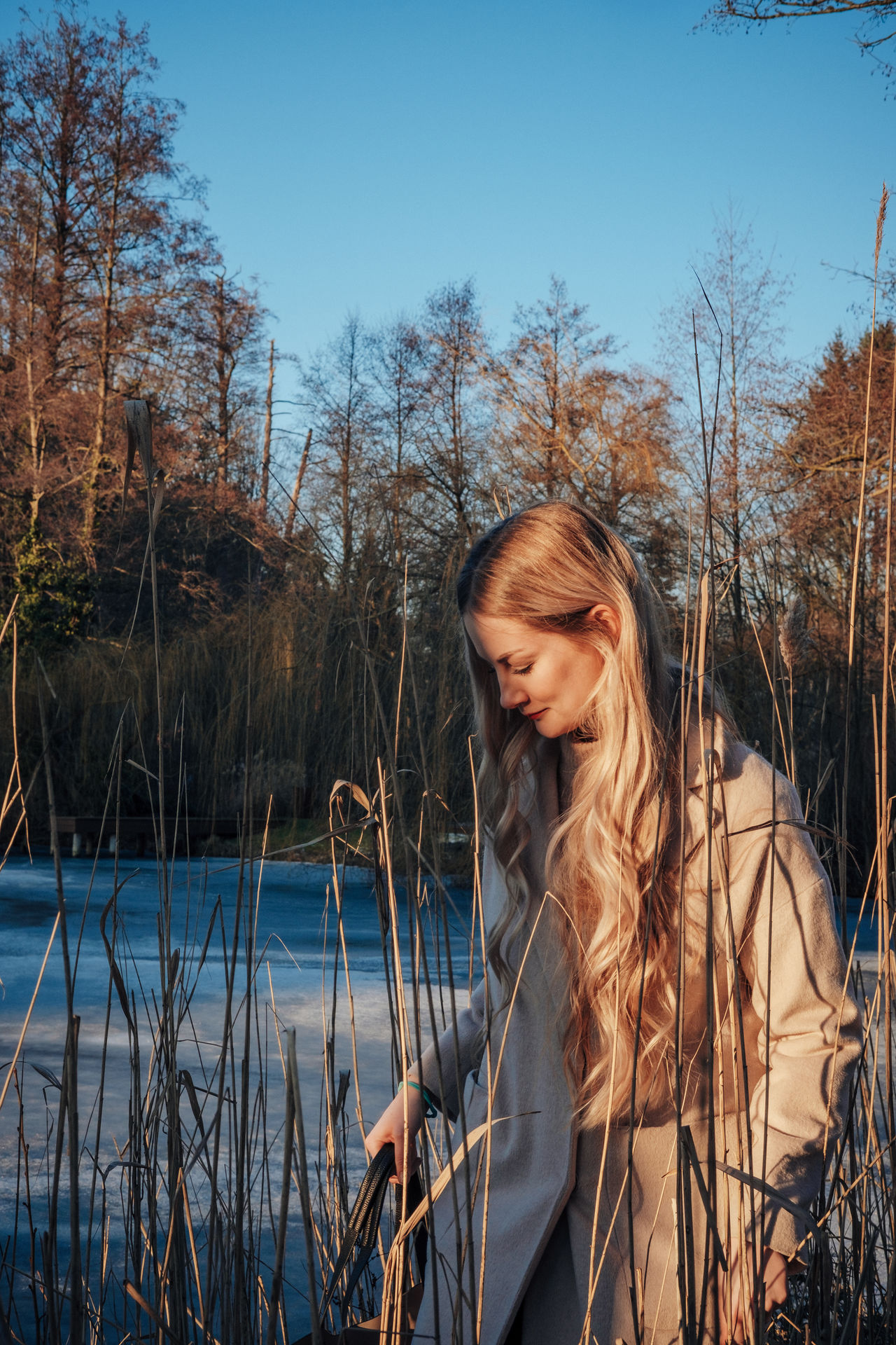 Catching the beautiful winter light. Adult Autumn Beauty In Nature Blond Hair Day Lake Leisure Activity Nature One Person One Woman Only One Young Woman Only Only Women Outdoors People Portrait Reed - Grass Family Sky Standing Tranquility Tree Waist Up Water Winter Women Young Adult