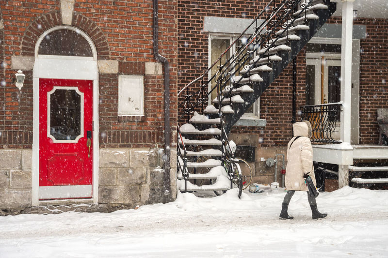 Snowstorm in Montreal. Pedestrian walking on a sidewalk. Adult Adults Only Architecture Brick Wall Building Exterior Cold Temperature Day Full Length Manual Worker One Man Only One Person Outdoors People Real People S Snow Snow ❄ Snowing Staircars Warm Clothing Winter Young Adult
