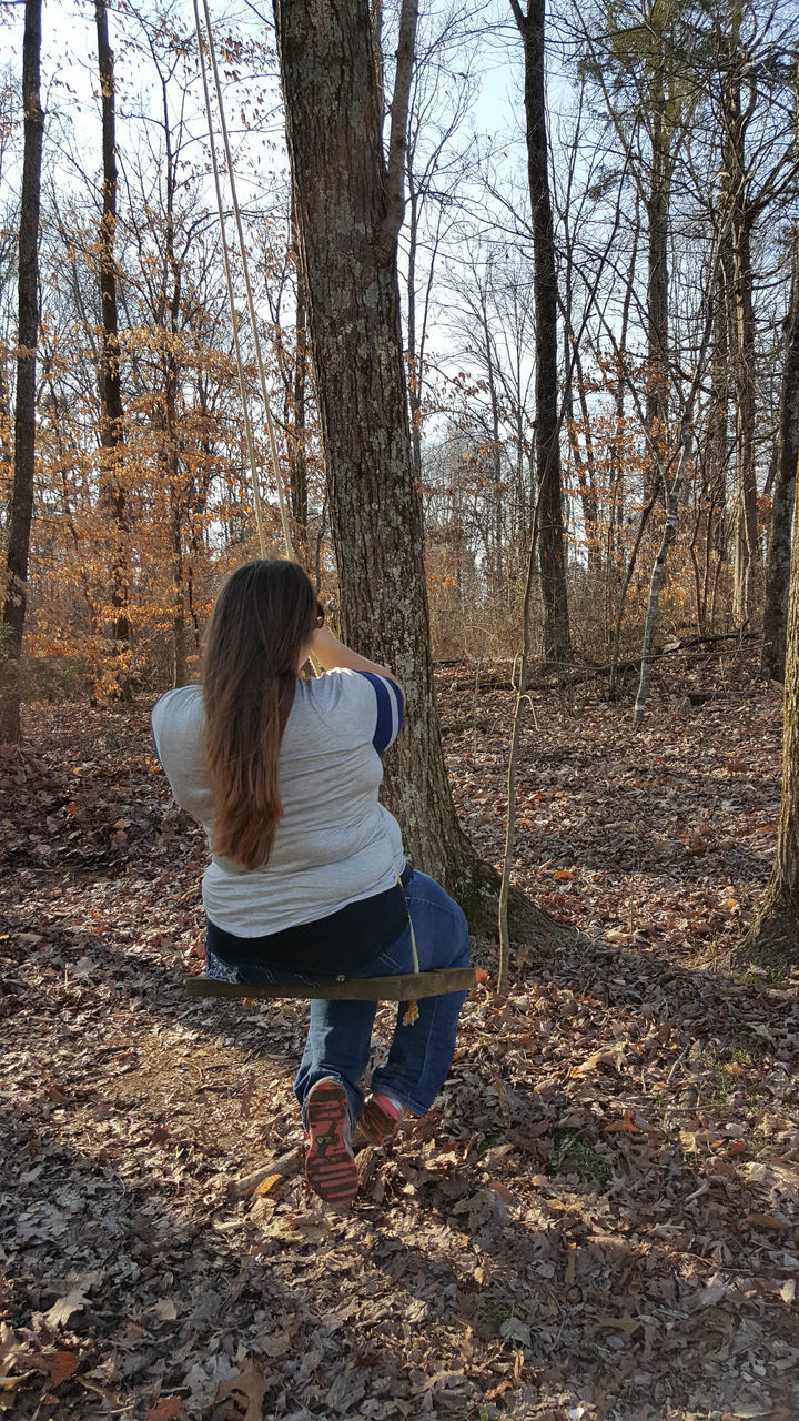 Rear View Of Woman Sitting On Rope Swing In Forest