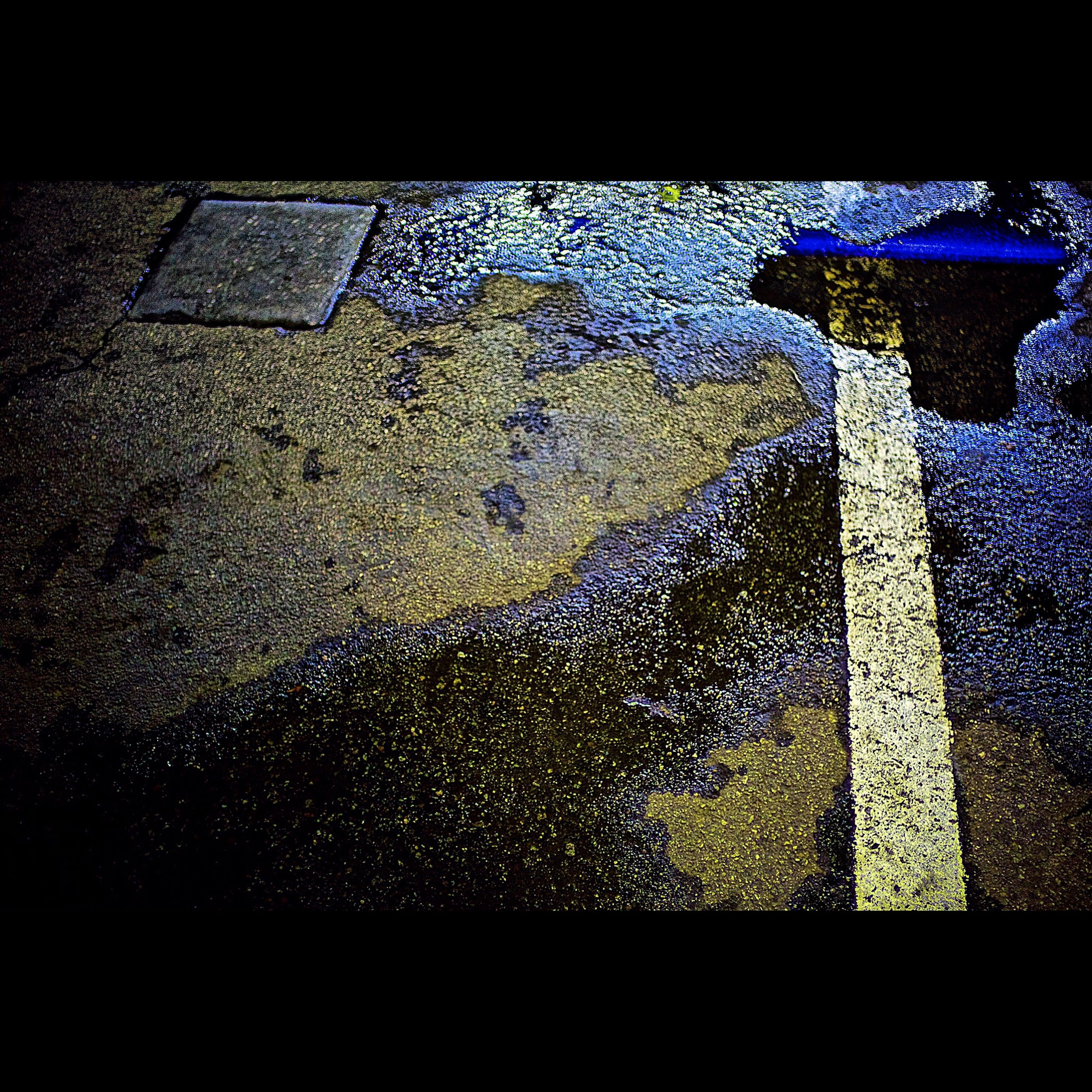 high angle view, street, shadow, close-up, water, built structure, day, wet, no people, outdoors, auto post production filter, blue, sunlight, architecture, textured, transportation, pattern, road, window