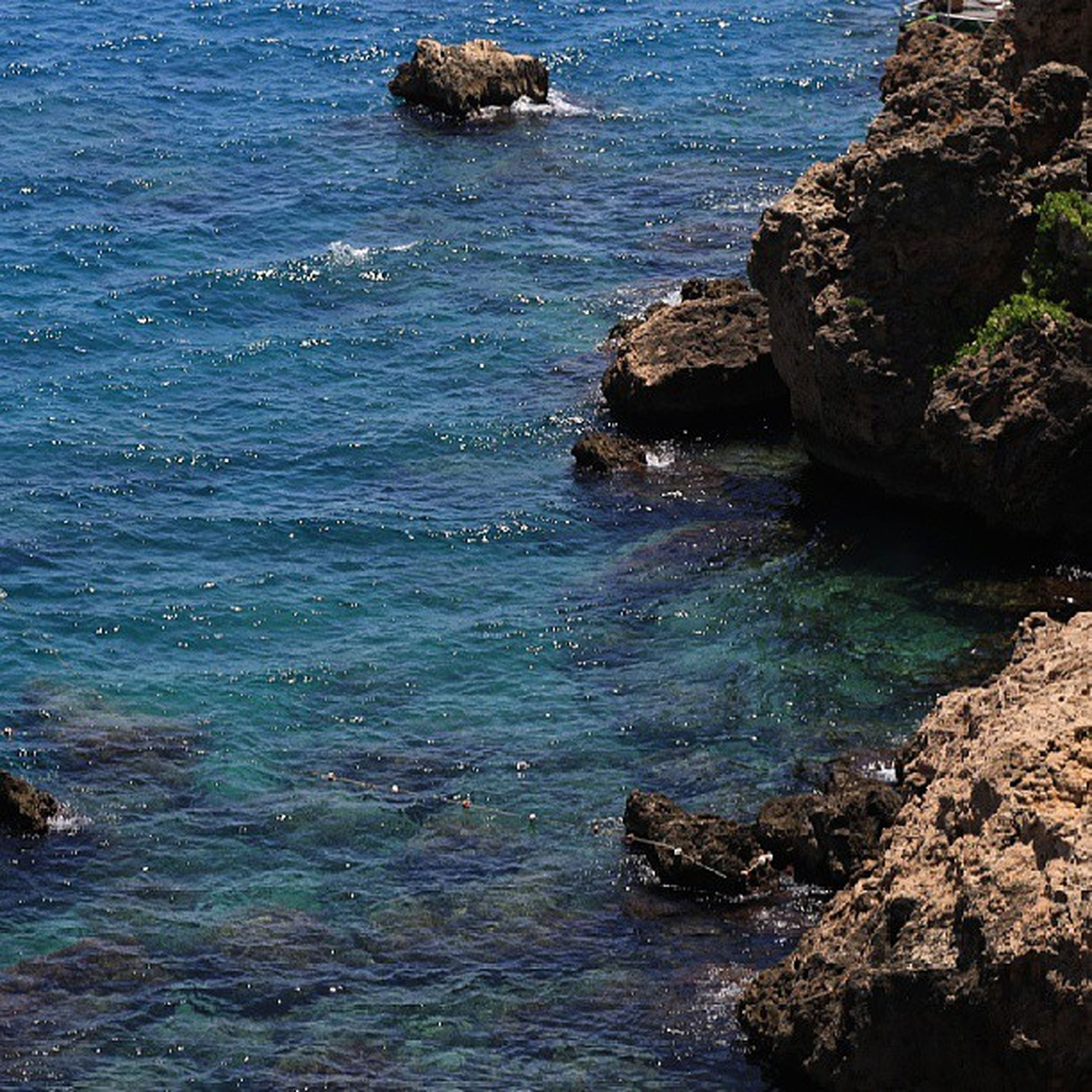 water, sea, rock - object, rock formation, beauty in nature, scenics, tranquility, tranquil scene, rock, nature, rippled, high angle view, cliff, idyllic, blue, day, coastline, horizon over water, seascape, no people